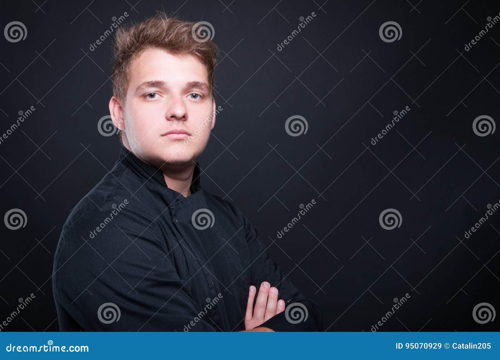 Stående av den unga kocken som poserar med vikta armar
