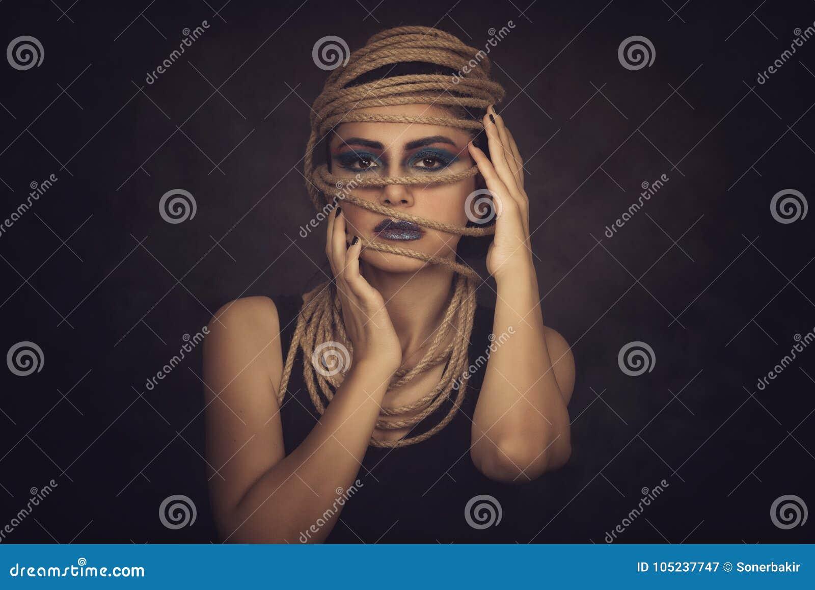 Stående av den unga kvinnan över rep med svart bakgrund Mode, utöver det vanliga makeup och begrepp för lyfta för framsida