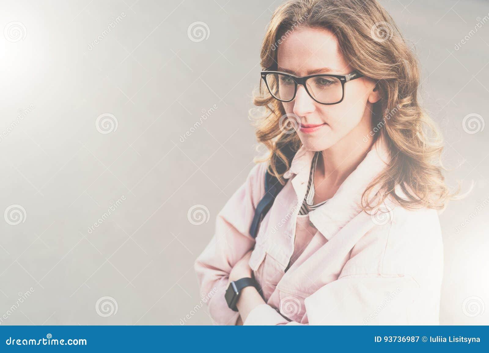 Stående av den unga kvinnan Hipsterflickan i exponeringsglas och rosa grov bomullstvillomslag står på stadsgatan och väntande på