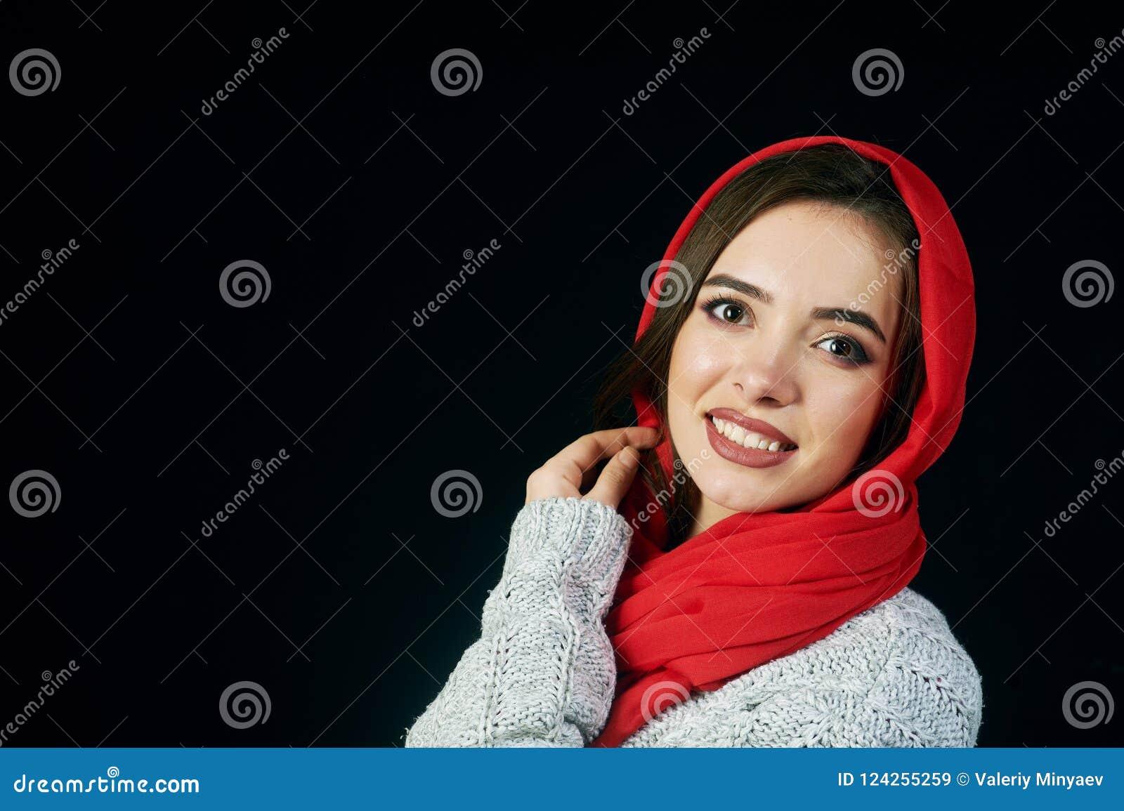 Stående av den unga kvinnan i hatt och omslag på mörk bakgrund