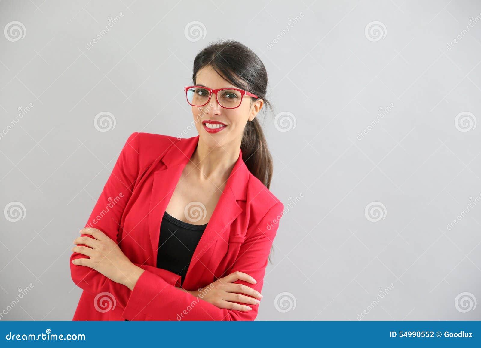 Stående av den unga kvinnan i rött omslag och rött glasögon