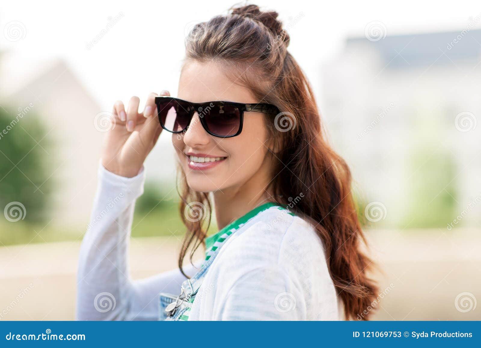 Stående av den unga kvinnan i solglasögon utomhus