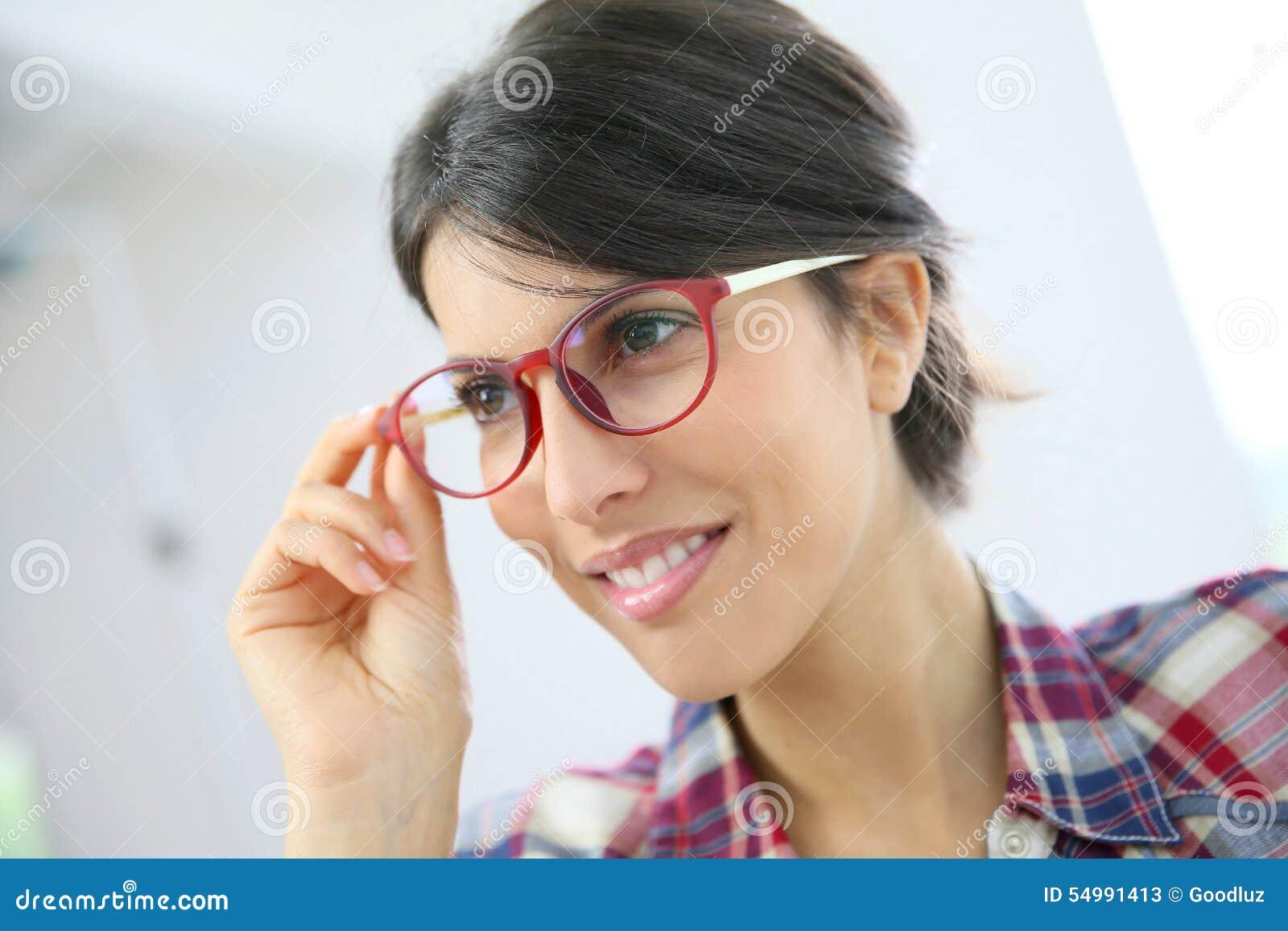 Stående av den unga kvinnan med rött glasögon