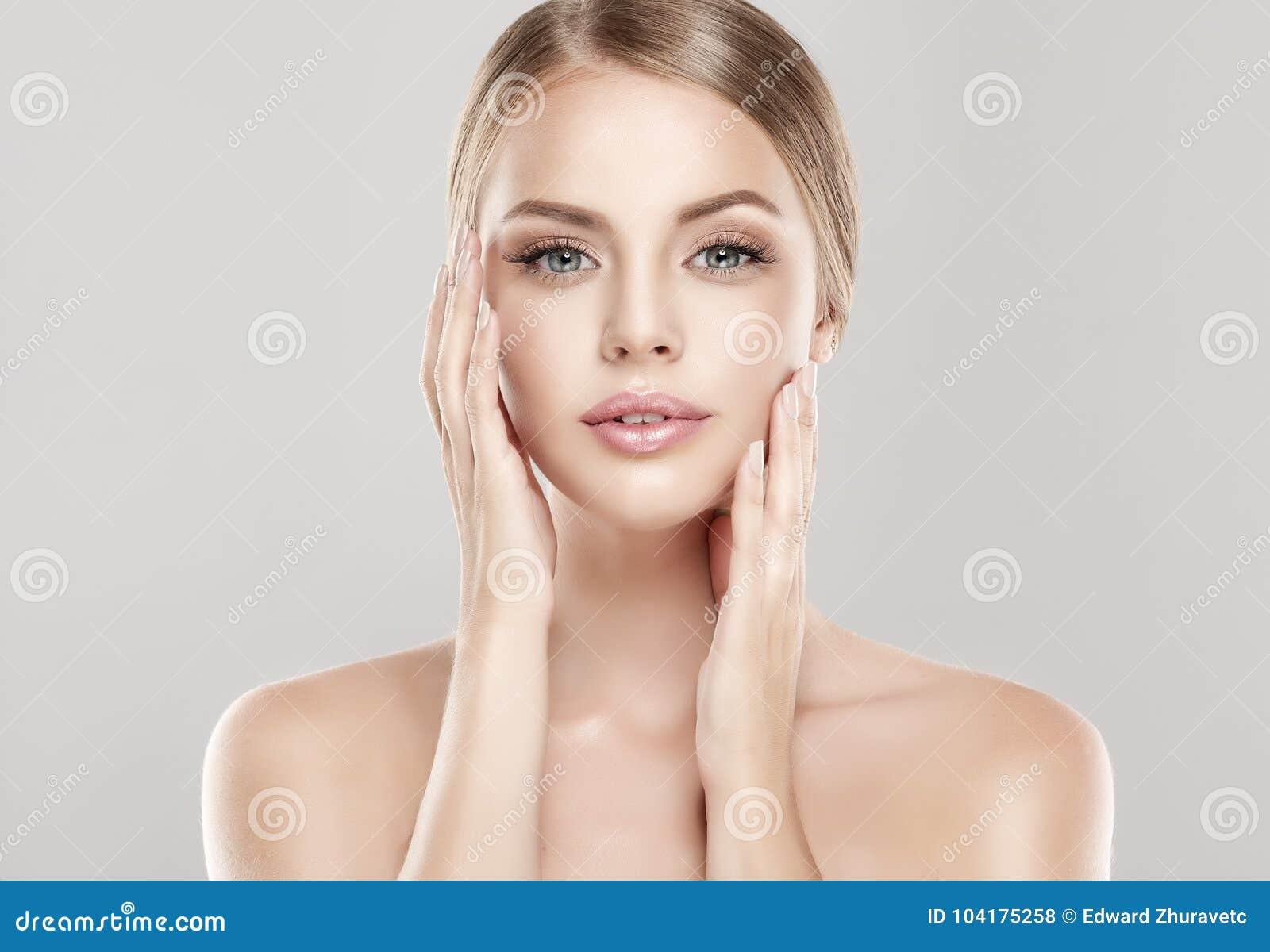 Stående av den unga kvinnan med ren ny hud och mjukt delikat smink Kvinnan är rörande ömt till egen framsida