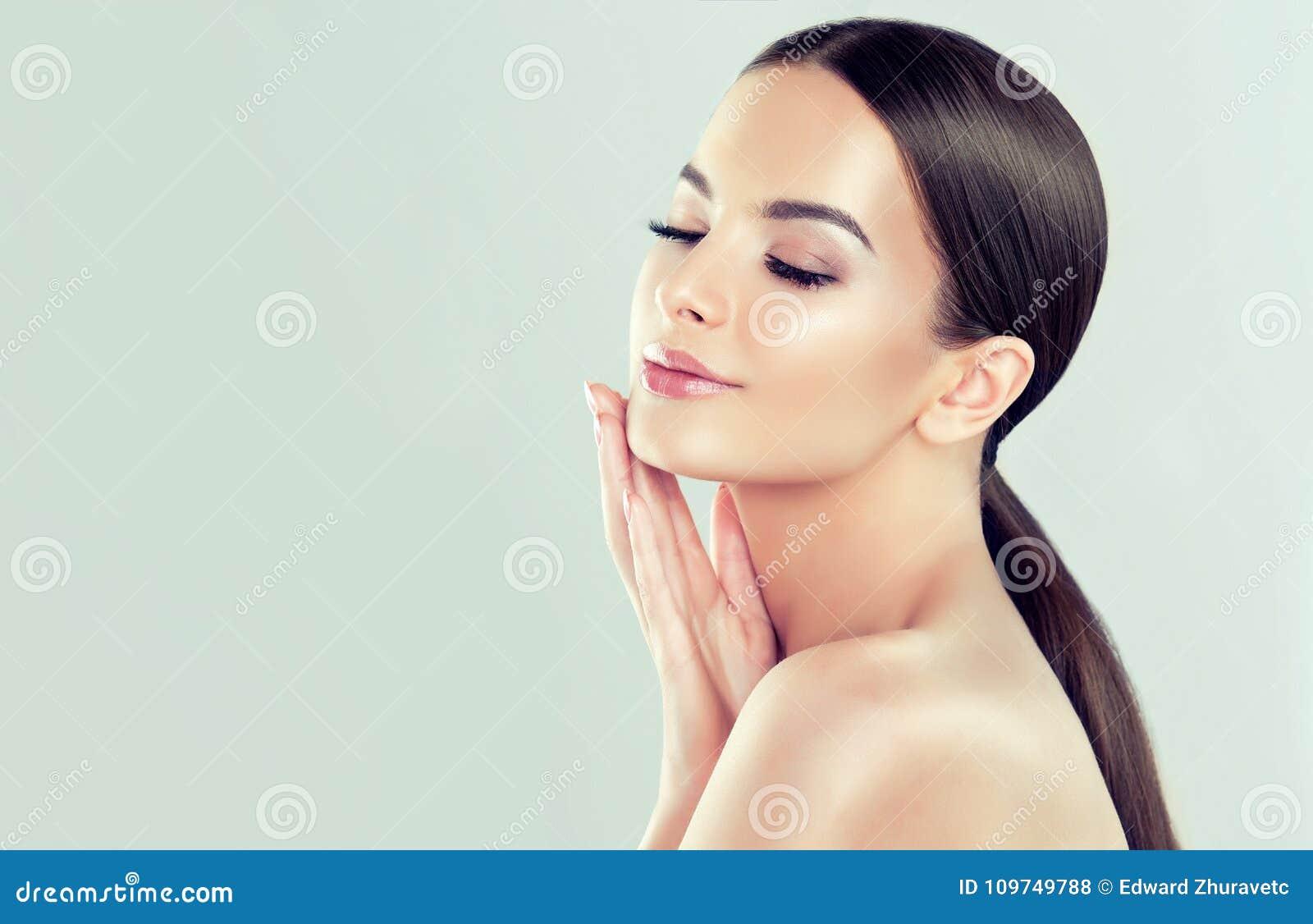 Stående av den unga kvinnan med ren ny hud och mjukt delikat smink Kvinnan är rörande till egen framsida ömt