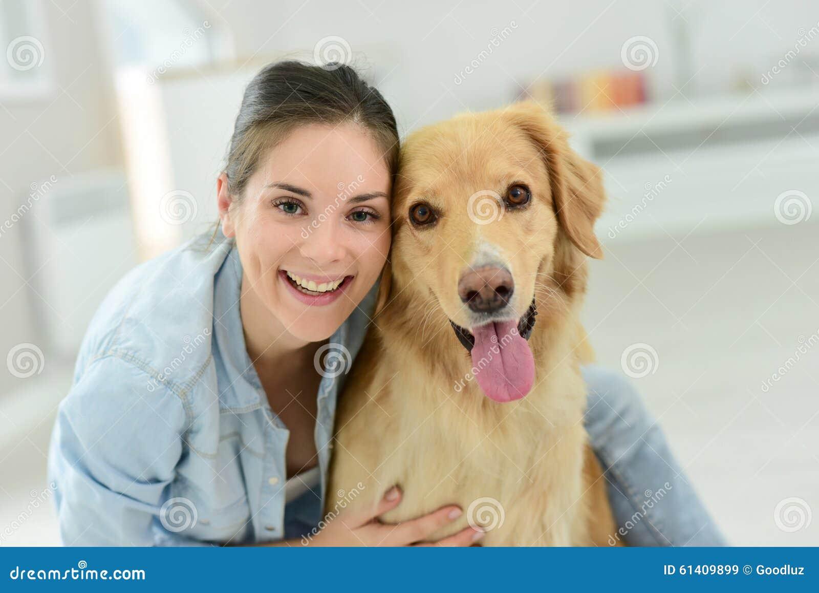 Stående av den unga kvinnan som daltar hennes hund