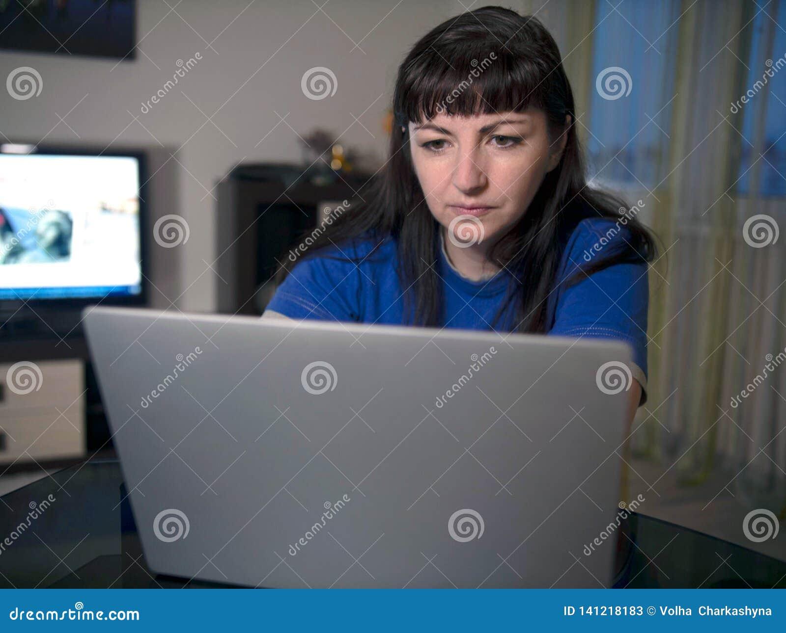 Stående av den unga kvinnan som hemma arbetar på bärbara datorn i aftonen