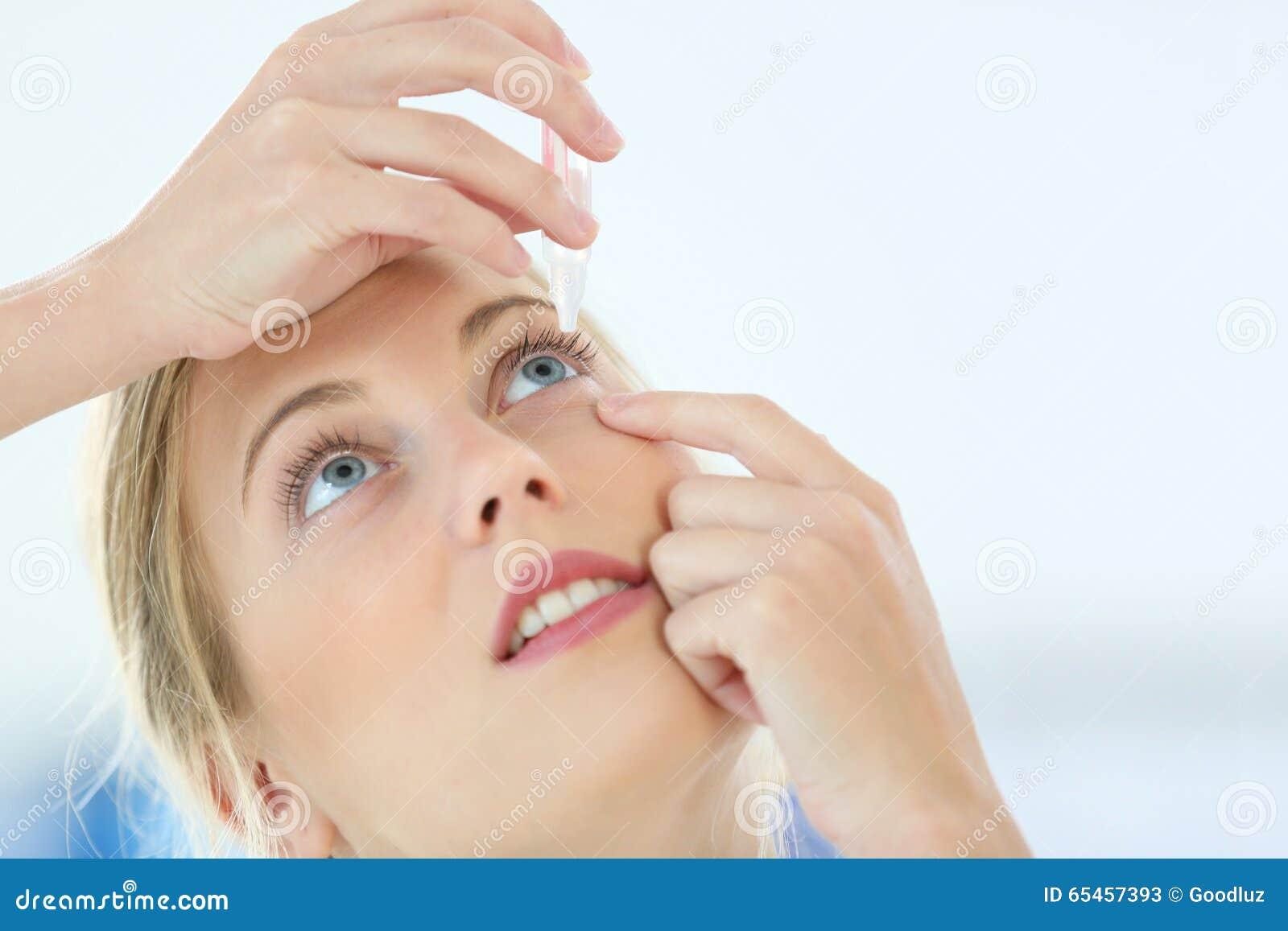 Stående av den unga kvinnan som sätter ögondroppar