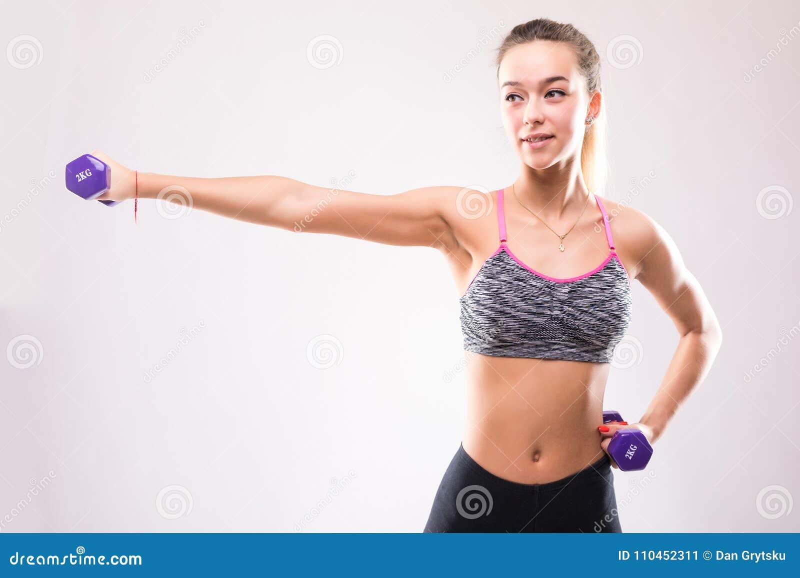 Stående av den unga lyckliga le kvinnan i sportswear som gör konditionövning med hantlar över vit bakgrund
