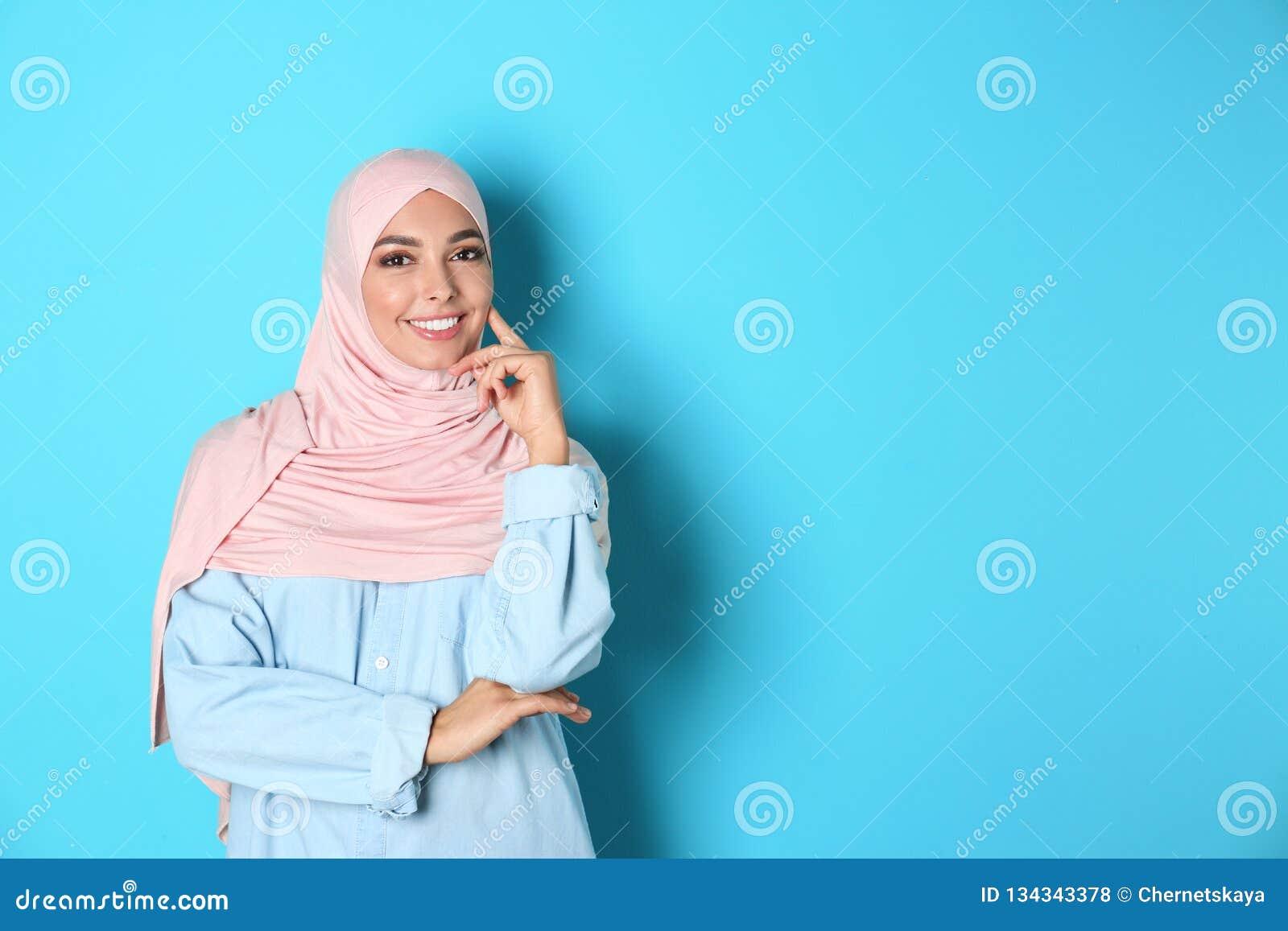 Stående av den unga muslimska kvinnan i hijab mot färgbakgrund