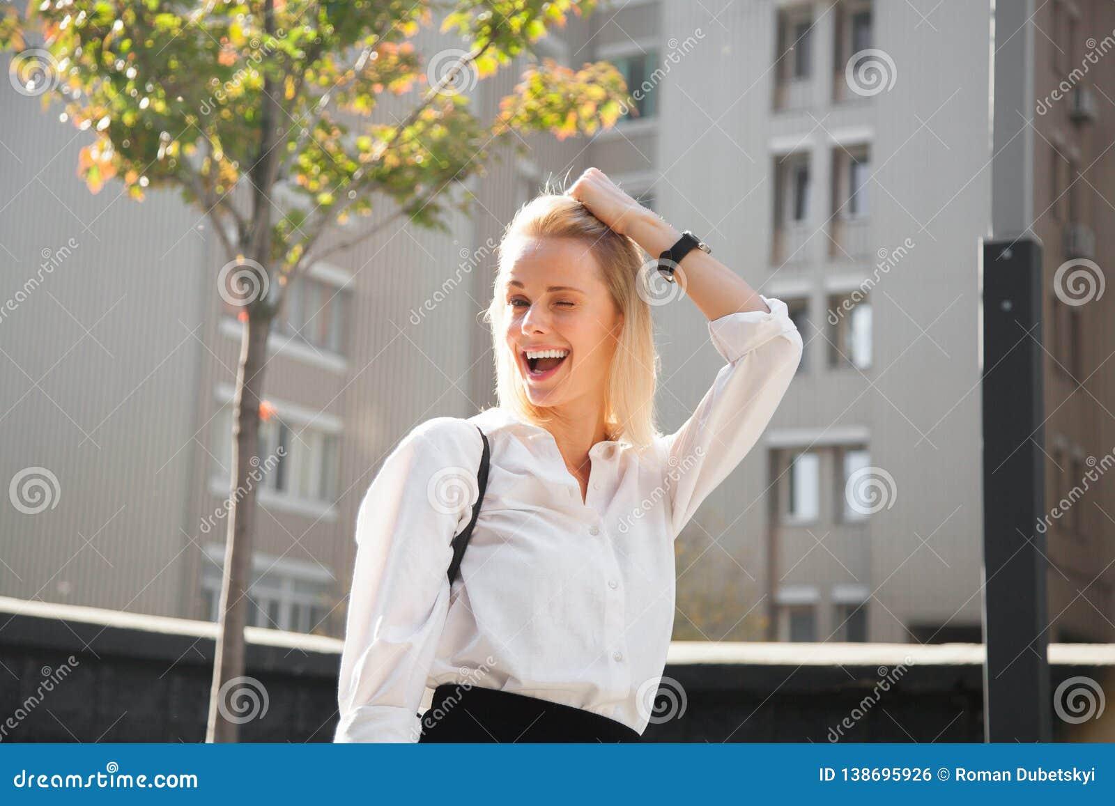 Stående av den unga skratta kvinnan i modern kläder som bedrar omkring att försöka på ny blick