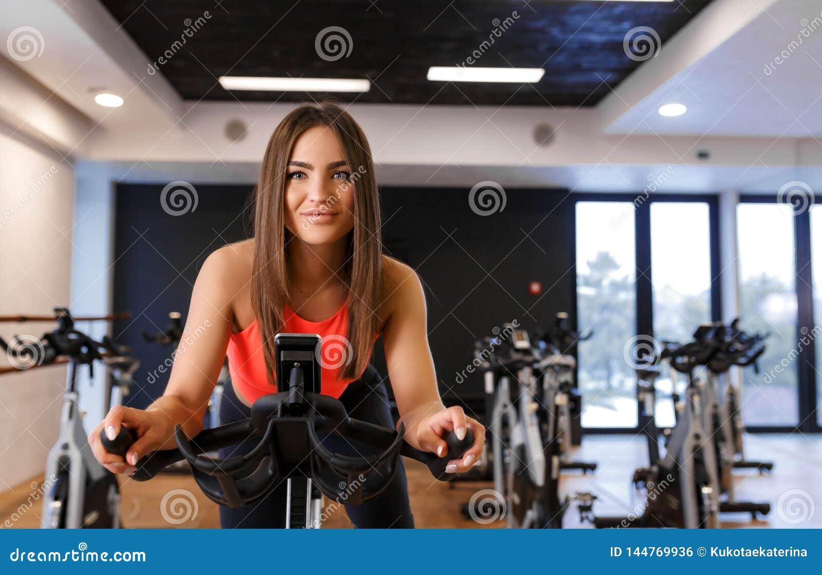 St?ende av den unga slanka kvinnan i sportweargenomk?rare p? motionscykelen i idrottshall Sport- och wellnesslivsstilbegrepp