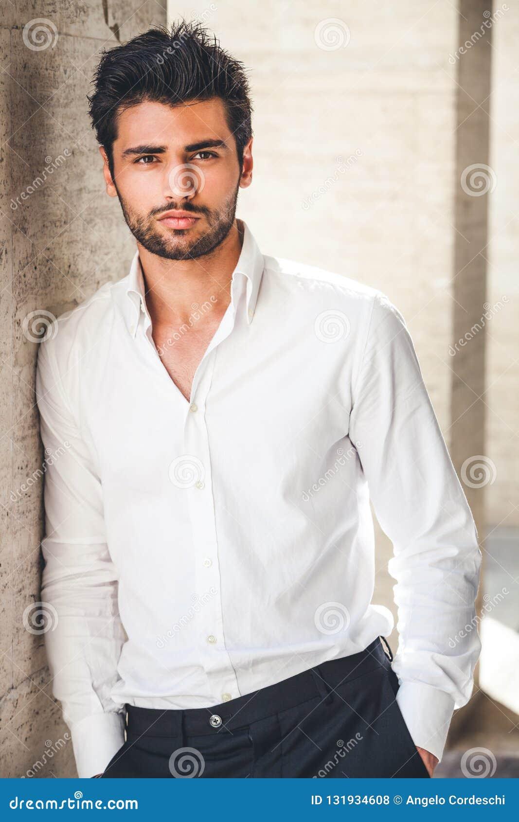 Stående av den unga stiliga mannen i den utomhus- vita skjortan