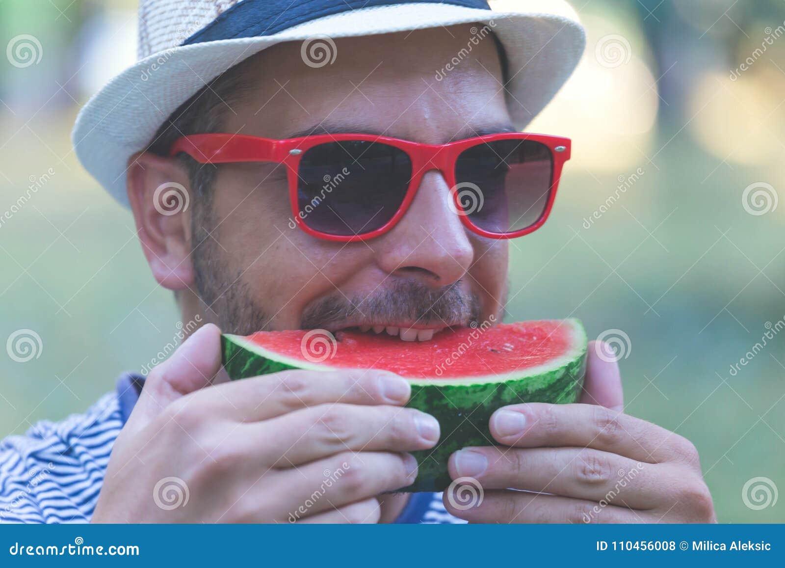 Stående av den unga stiliga mannen som äter vattenmelon, hållande vattenmelon för man