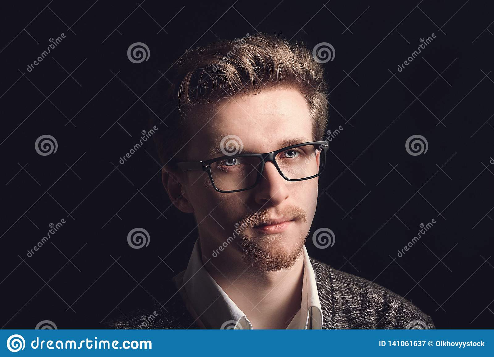 Stående av den unga tillfälliga mannen med exponeringsglas som framme ler av kamera Ung stilig man i marinskjorta och exponerings