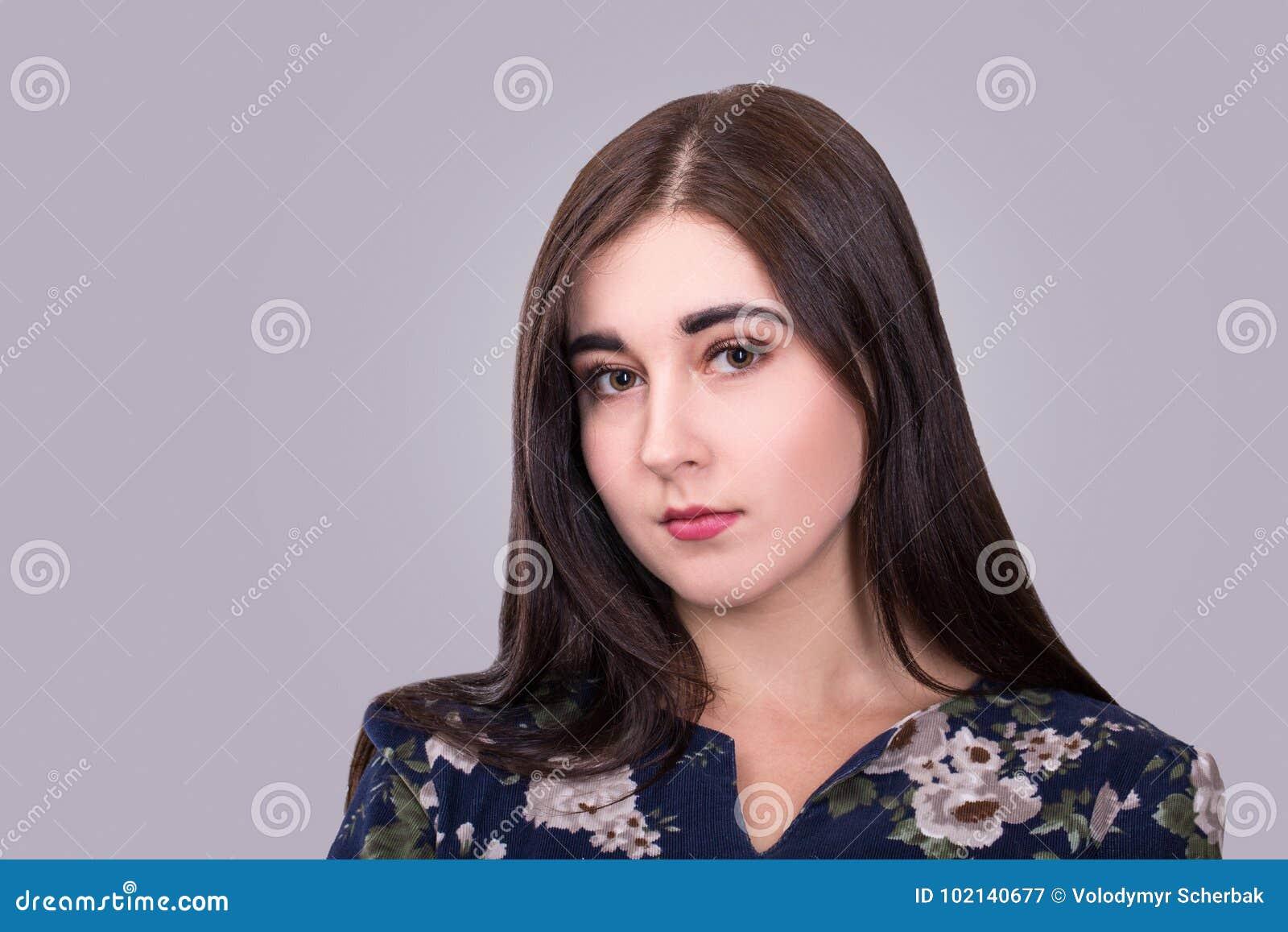 Stående av den ursnygga unga kvinnan på grå bakgrund