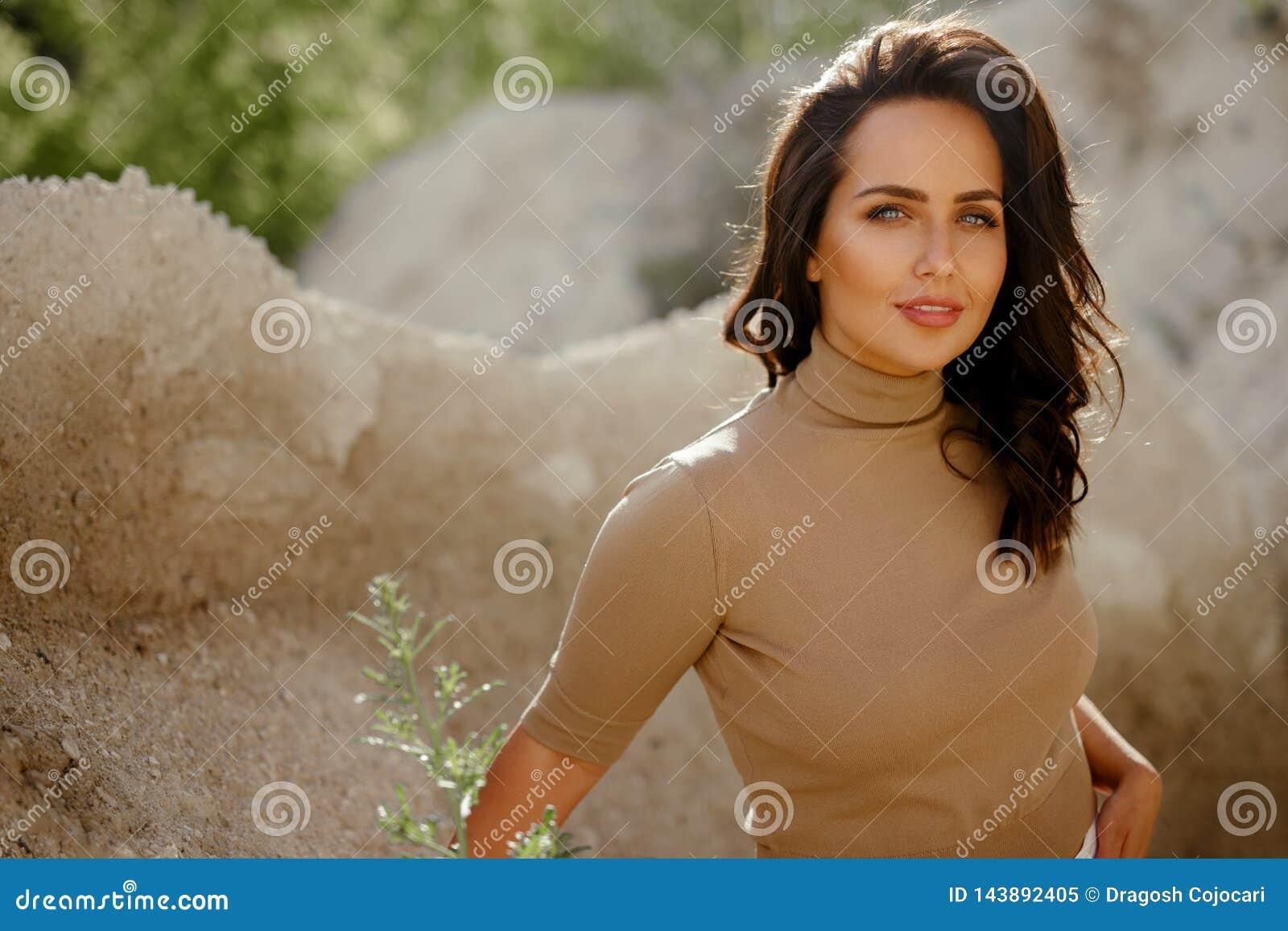 Stående av den ursnygga unga kvinnan som ser kameraanseende i natur, med kopieringsutrymme pärlor för blå för begrepp för bakgrun