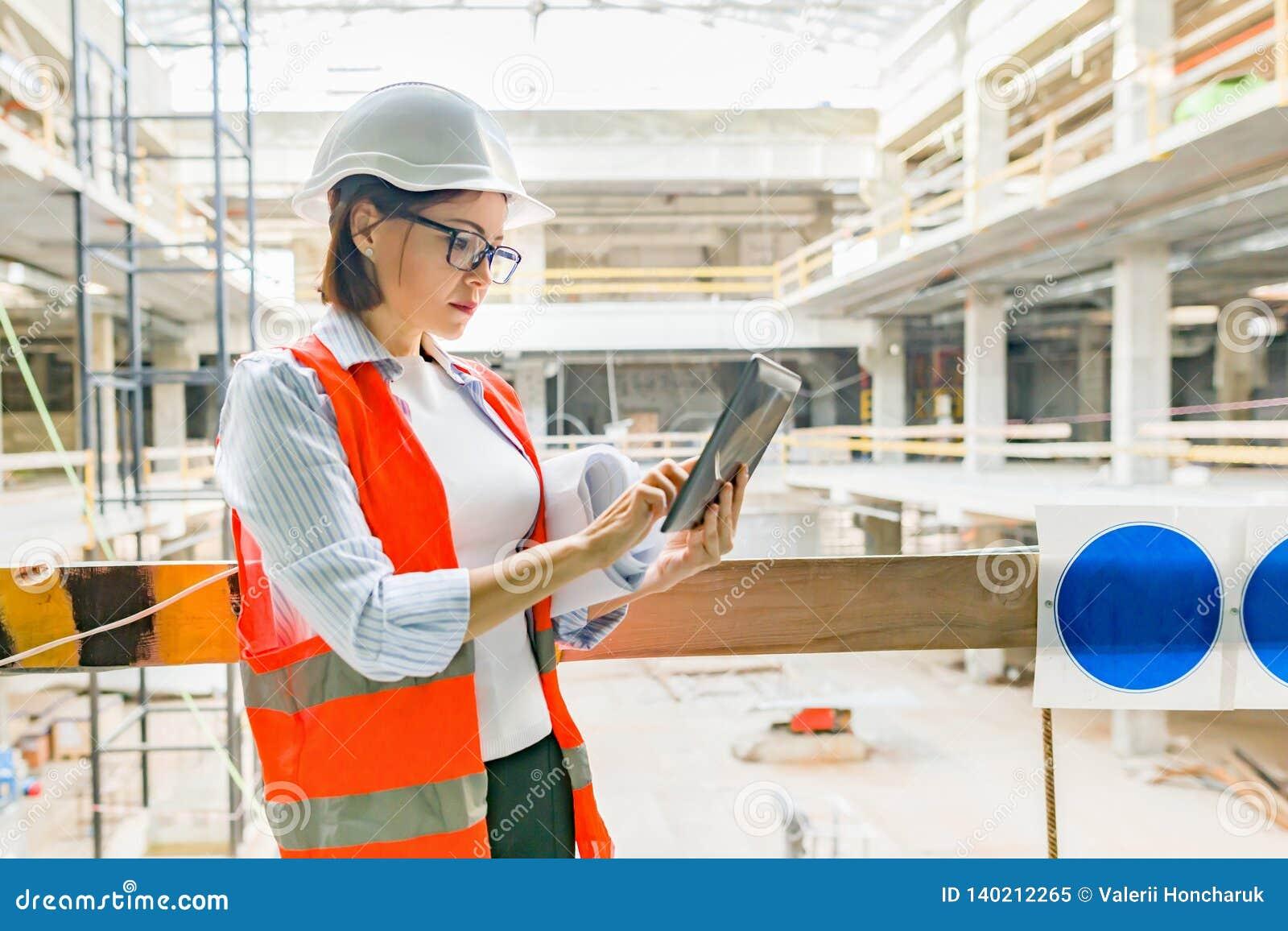 Stående av den vuxna kvinnliga byggmästaren, tekniker, arkitekt, inspektör, chef på konstruktionsplatsen Kvinna med plan, digital