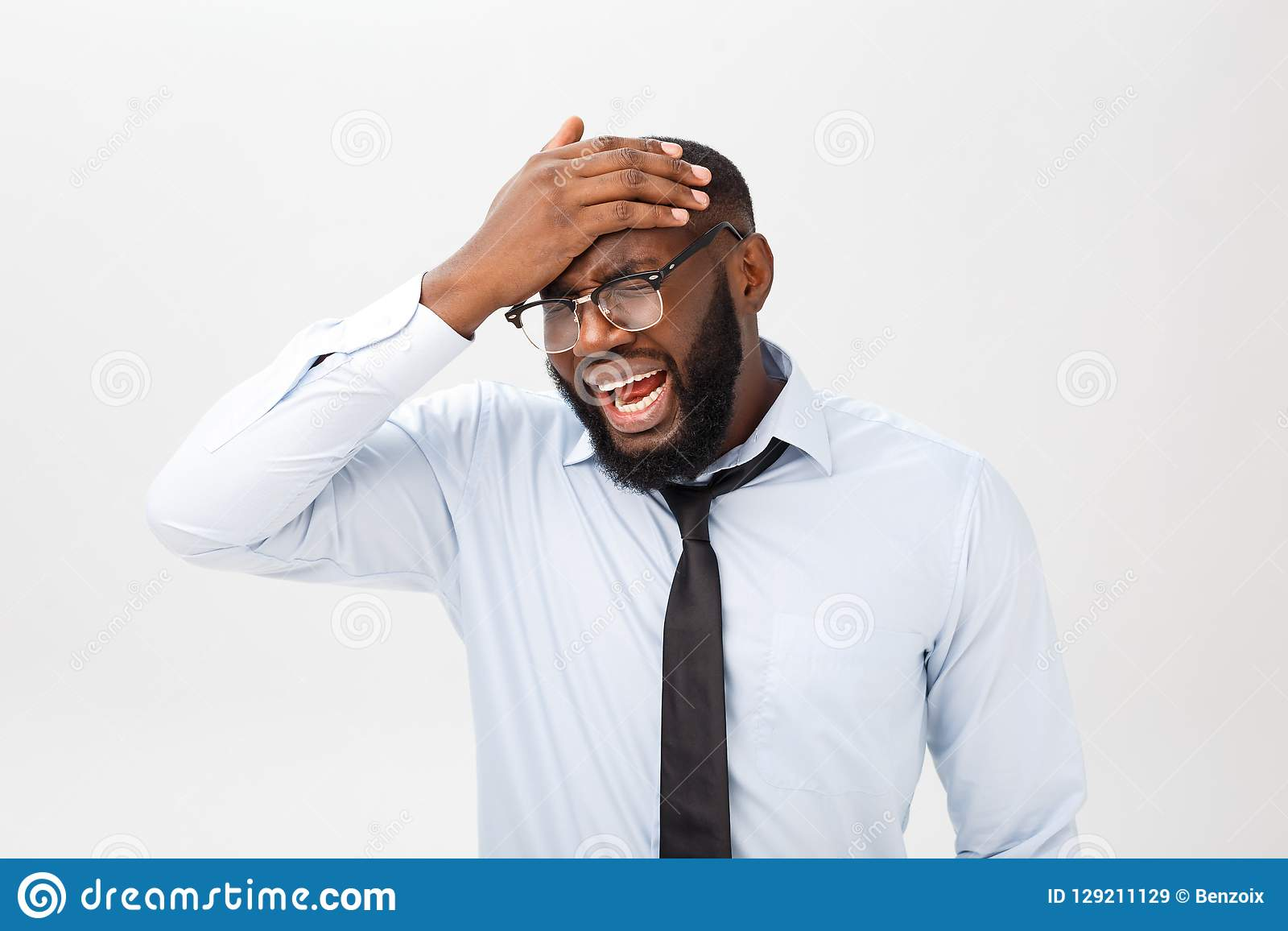 Stående av desperat förargat svart manligt skrika i ursinne och ilska som ut river hans hår, medan känna sig rasande och tokigt
