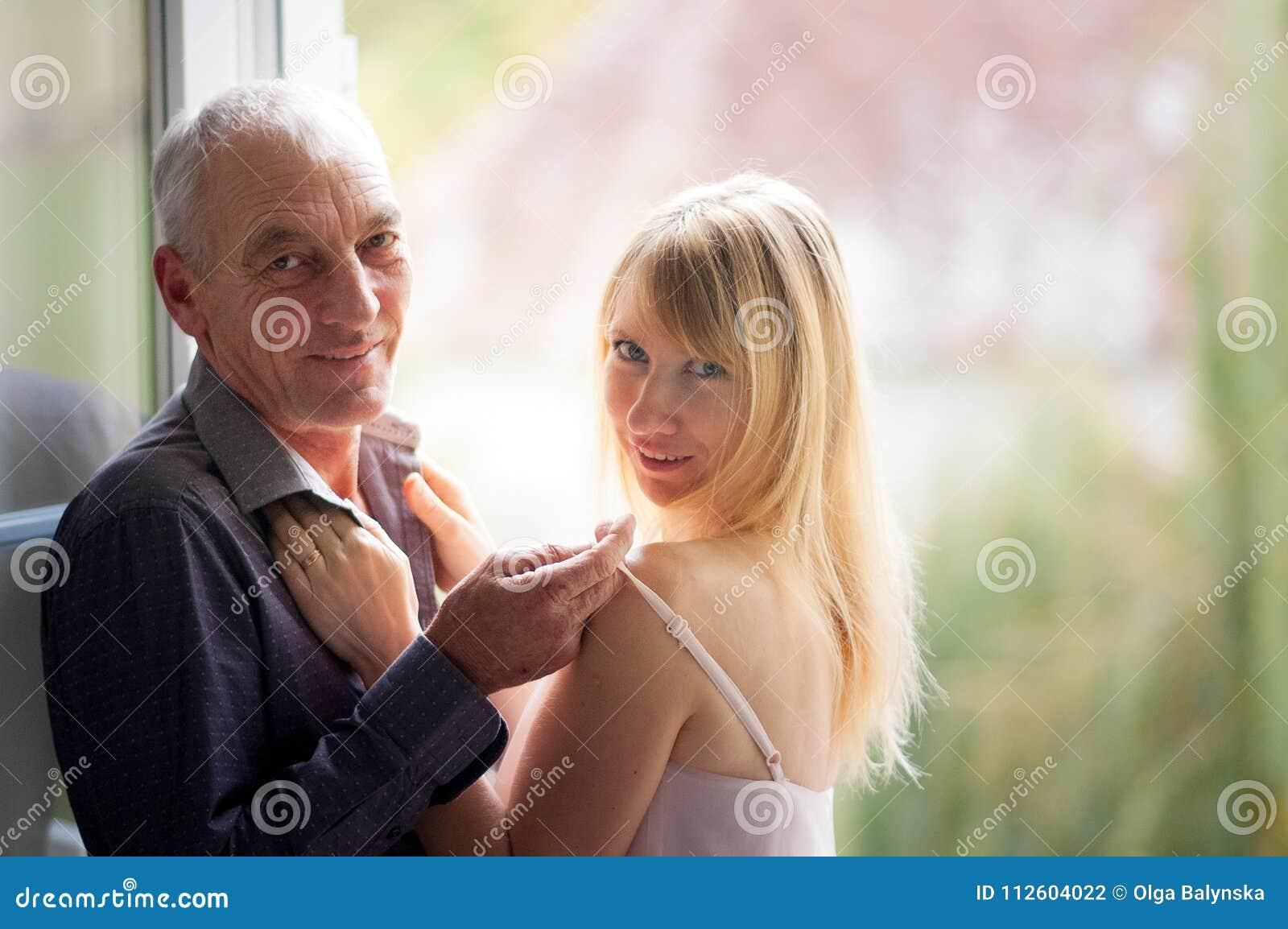 Stående av det äldre mananseendet nära fönstret med hans unga Blondin-haired fru i sommarkortslutningsklänning Par med