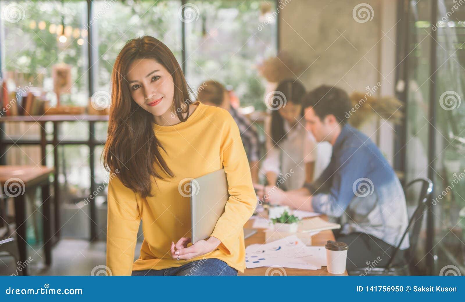 Stående av det coworking kontoret för asiatiskt kvinnligt funktionsdugligt lag, le av lycklig beautif ul-kvinna i modernt kontor