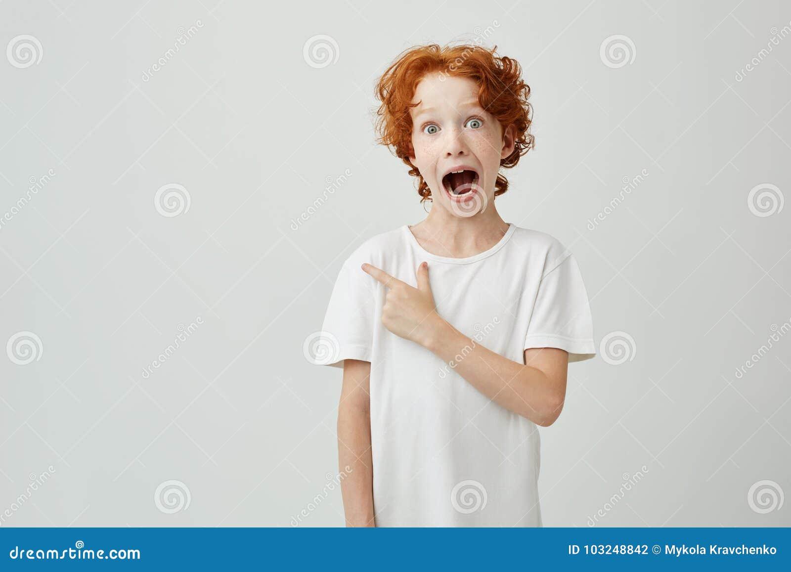 Stående av det glade ljust rödbrun barnet med fräknar som poserar med den öppnade munnen och galet uttryck som pekar på fritt utr