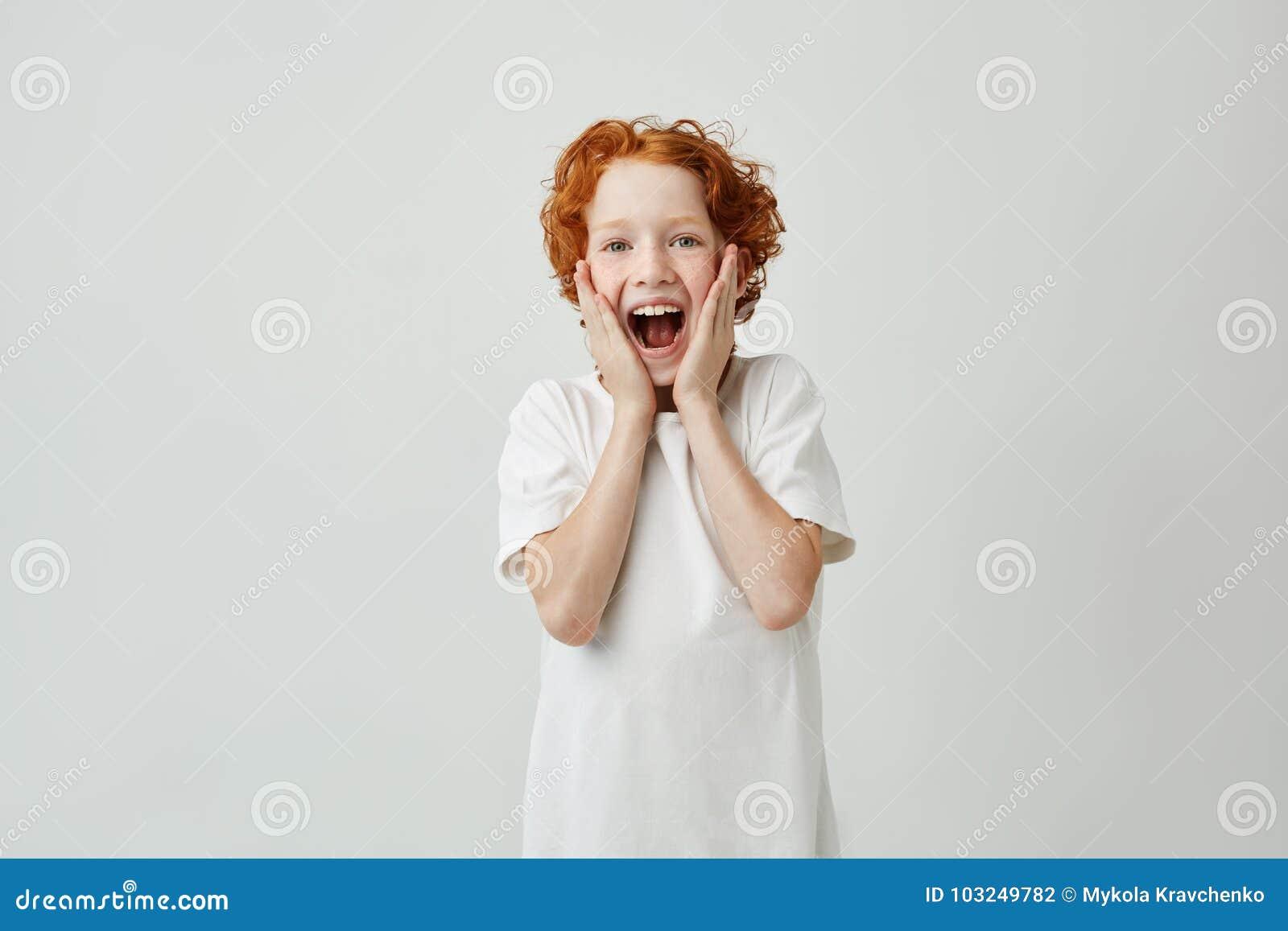 Stående av det gulliga röda haired barnet som skriker med lyckligt uttryck, när fadern gav honom den lilla valpen som jul