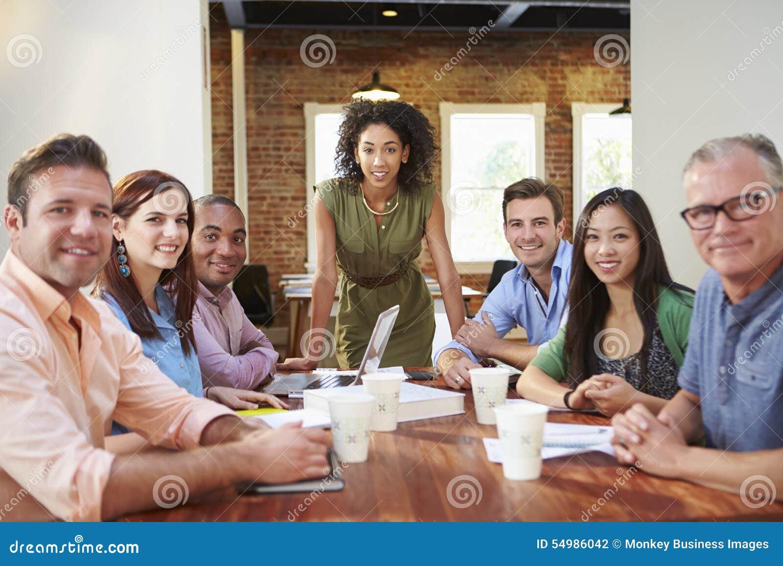 Stående av det kvinnliga framstickandet With Team In Meeting