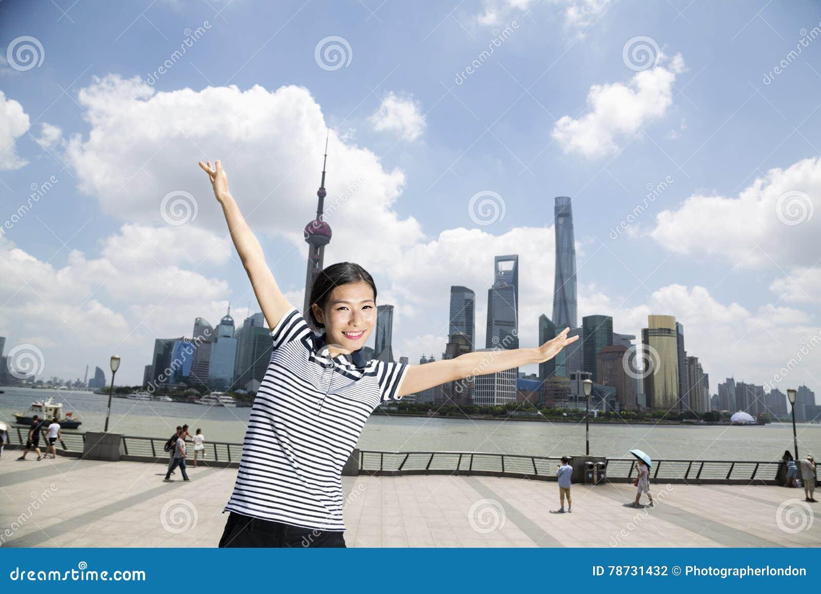 Stående av det lyckliga kvinnaanseendet med armar som är utsträckta på promenad mot Pudong horisont