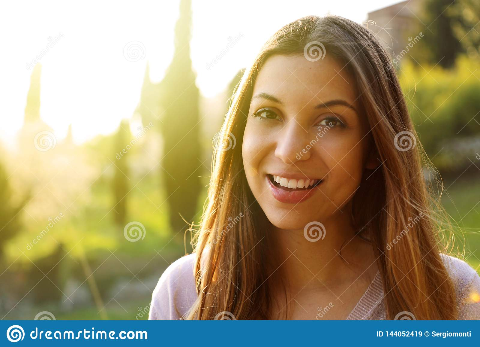 Stående av det lyckliga le kvinnaanseendet på solig sommar eller vårdag utanför Gullig le kvinna som ser till den filtrerade sida