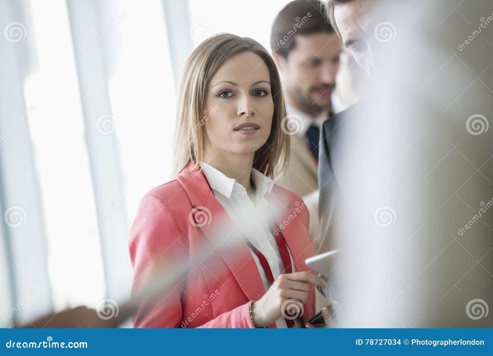 Stående av det säkra affärskvinnaanseendet med kollegor i ljust tänd konventcentrum