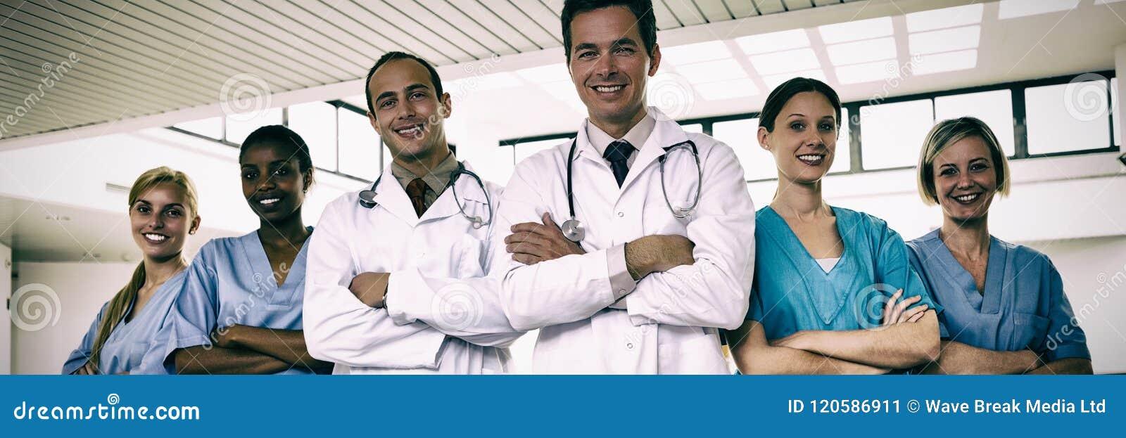 Stående av doktorer och sjuksköterskor med korsade armar