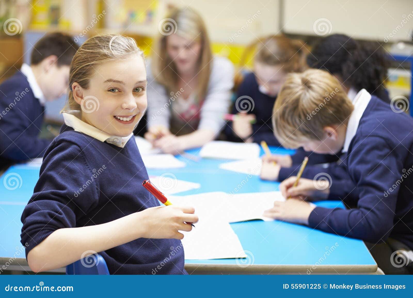 Stående av eleven i klassrum med läraren