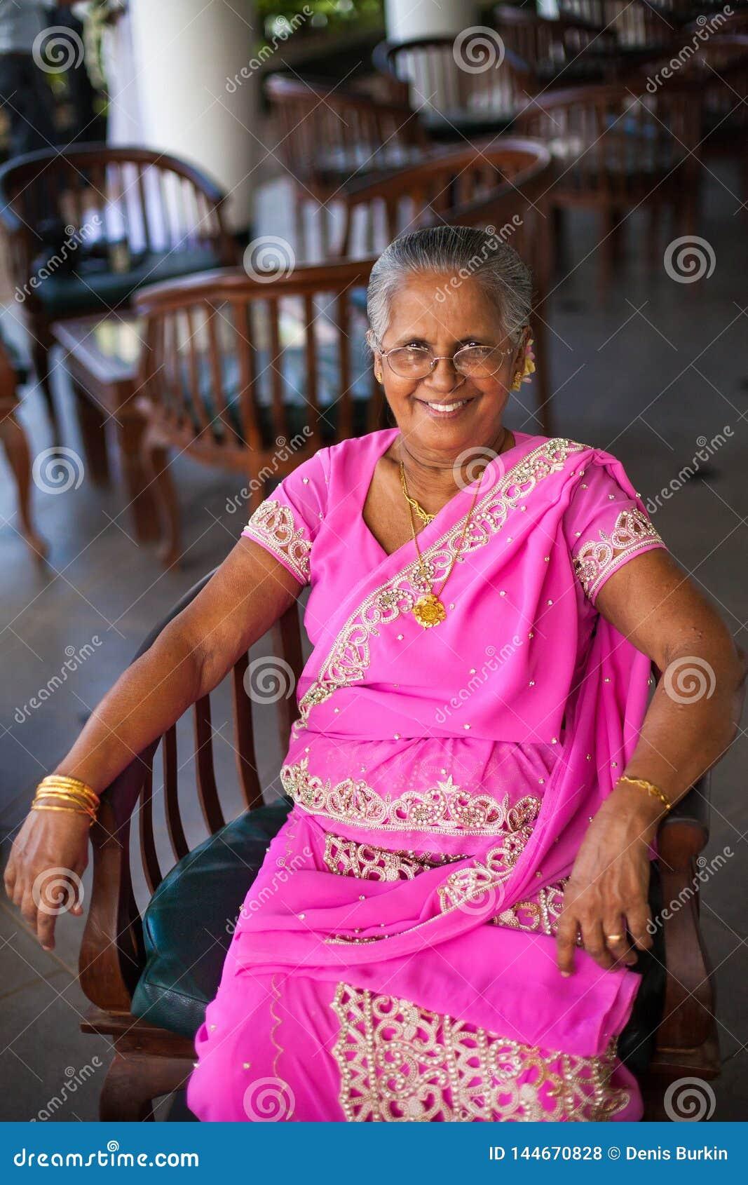 Stående av en äldre indisk lycklig kvinna i en festlig nationell sari