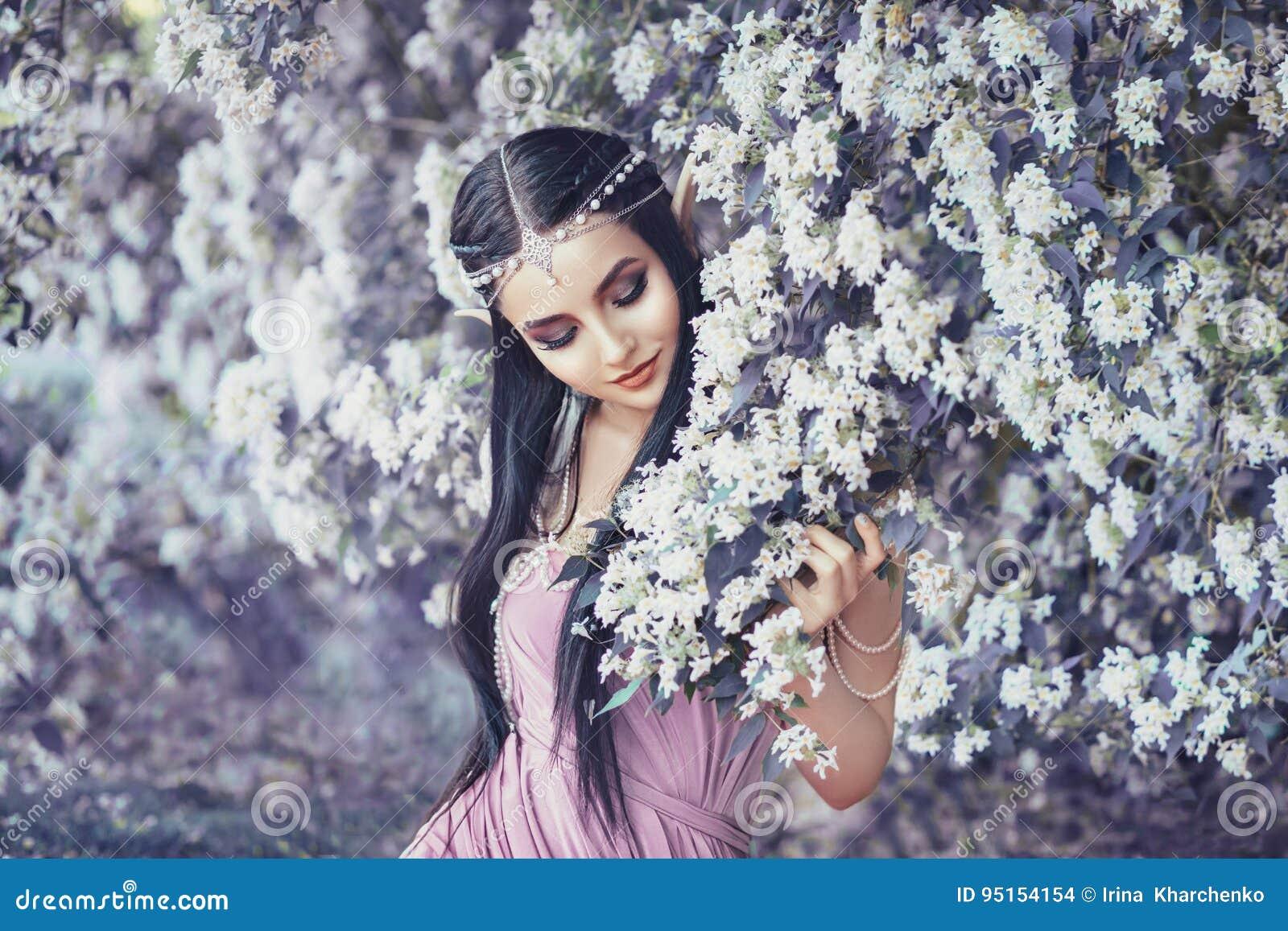 Stående av en älva i en blommande trädgård