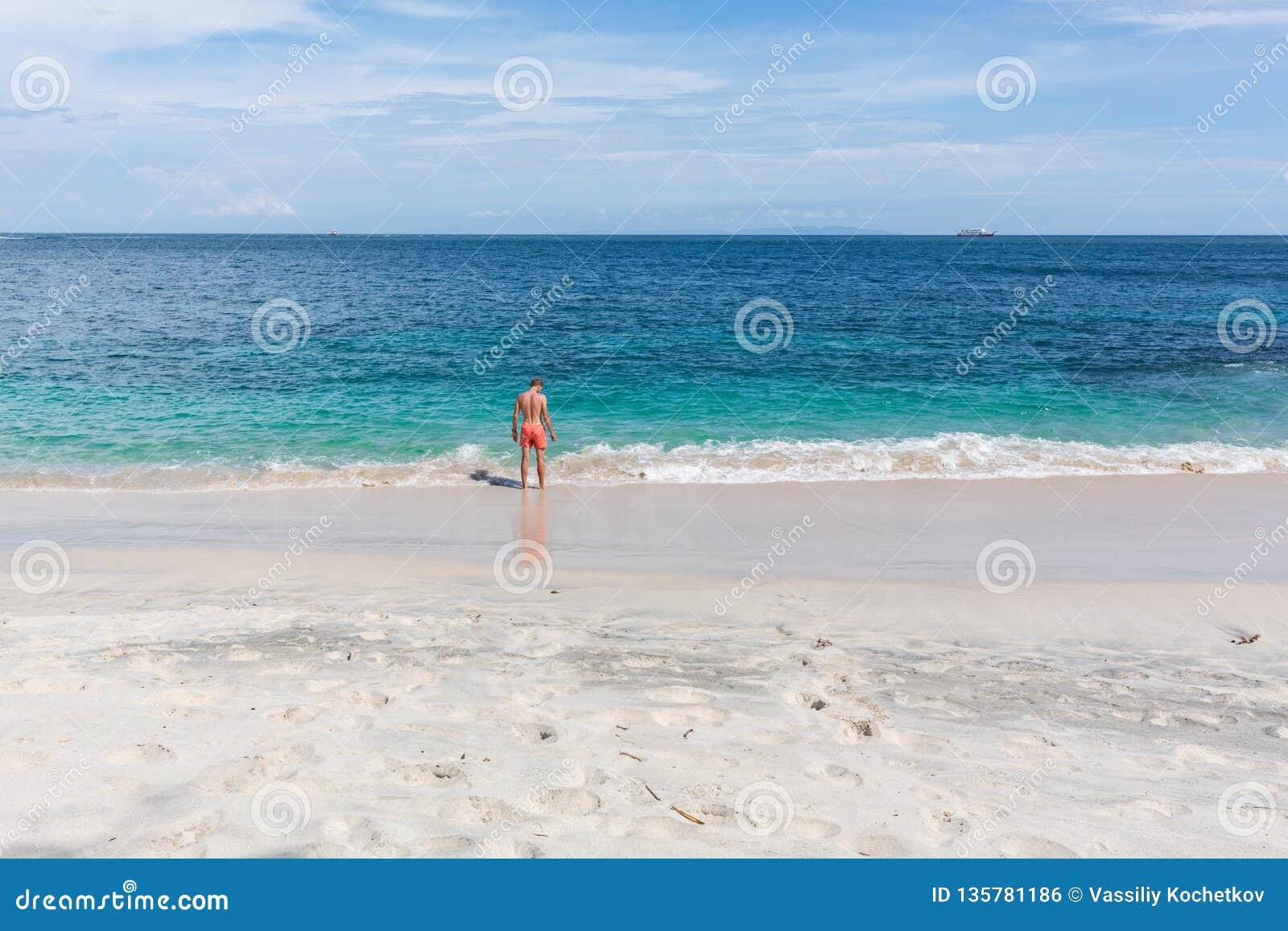 Stående av en attraktiv ung man på en tropisk strand