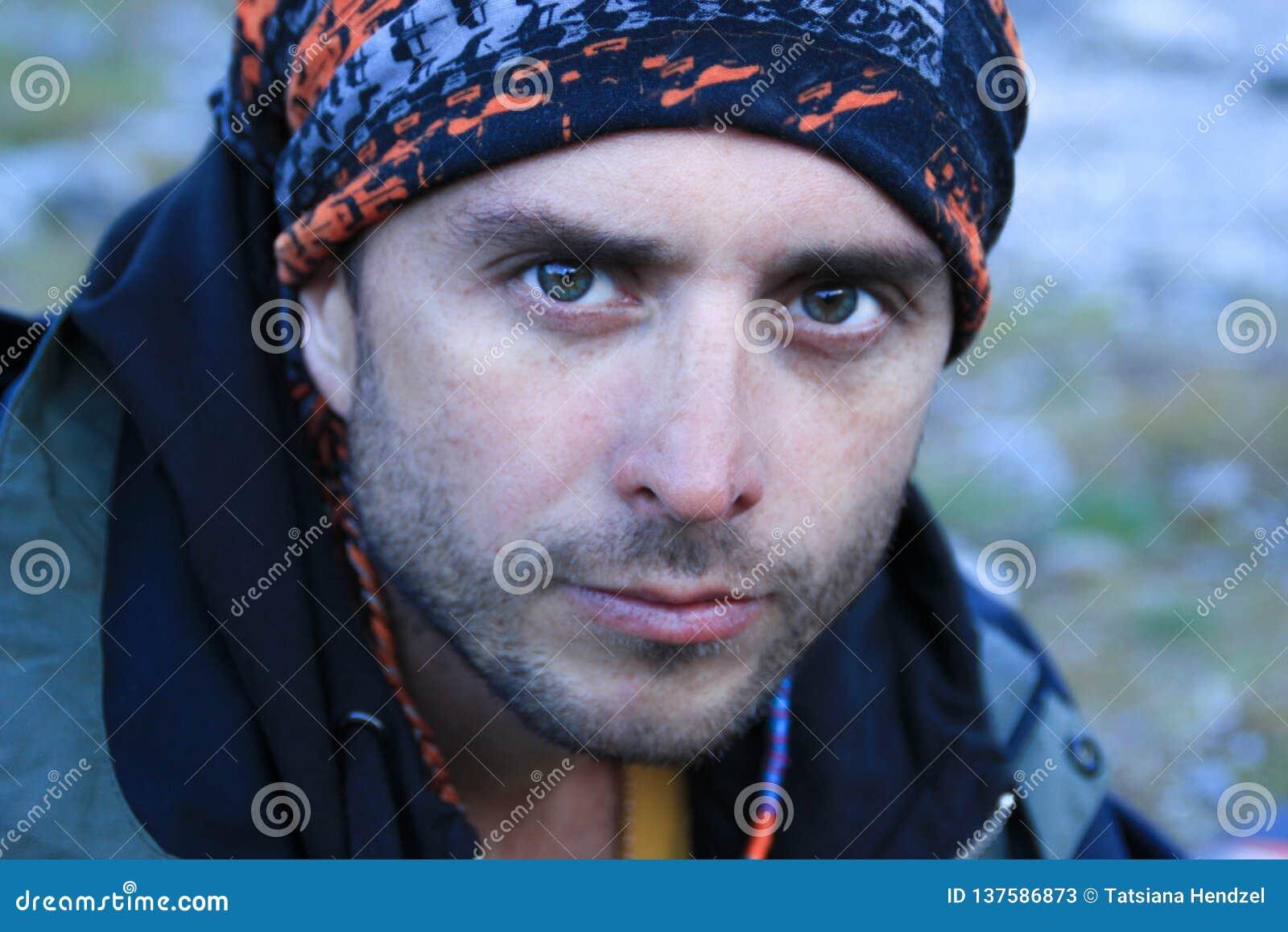 Stående av en attraktiv ung vit Caucasian manlig turist med en allvarlig framsida och klara blåa ögon i ett turist- omslag och fa