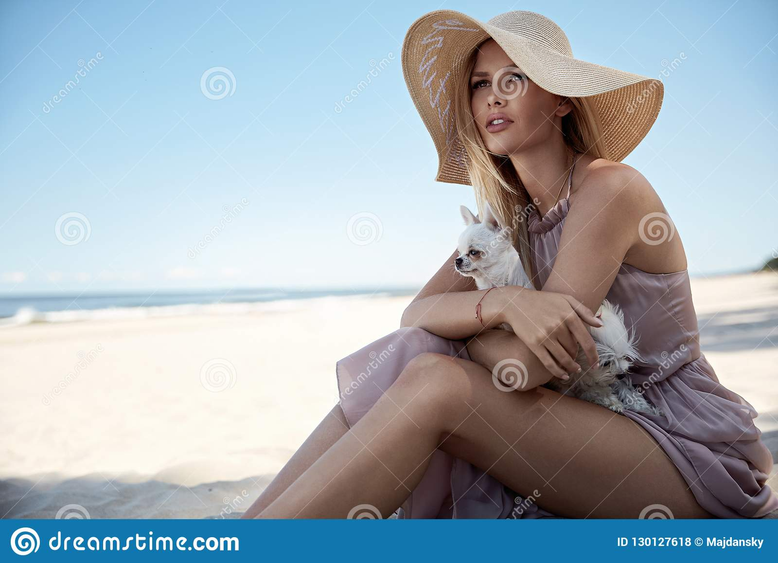 Stående av en elegant kvinna som kopplar av på en strand med hennes belove