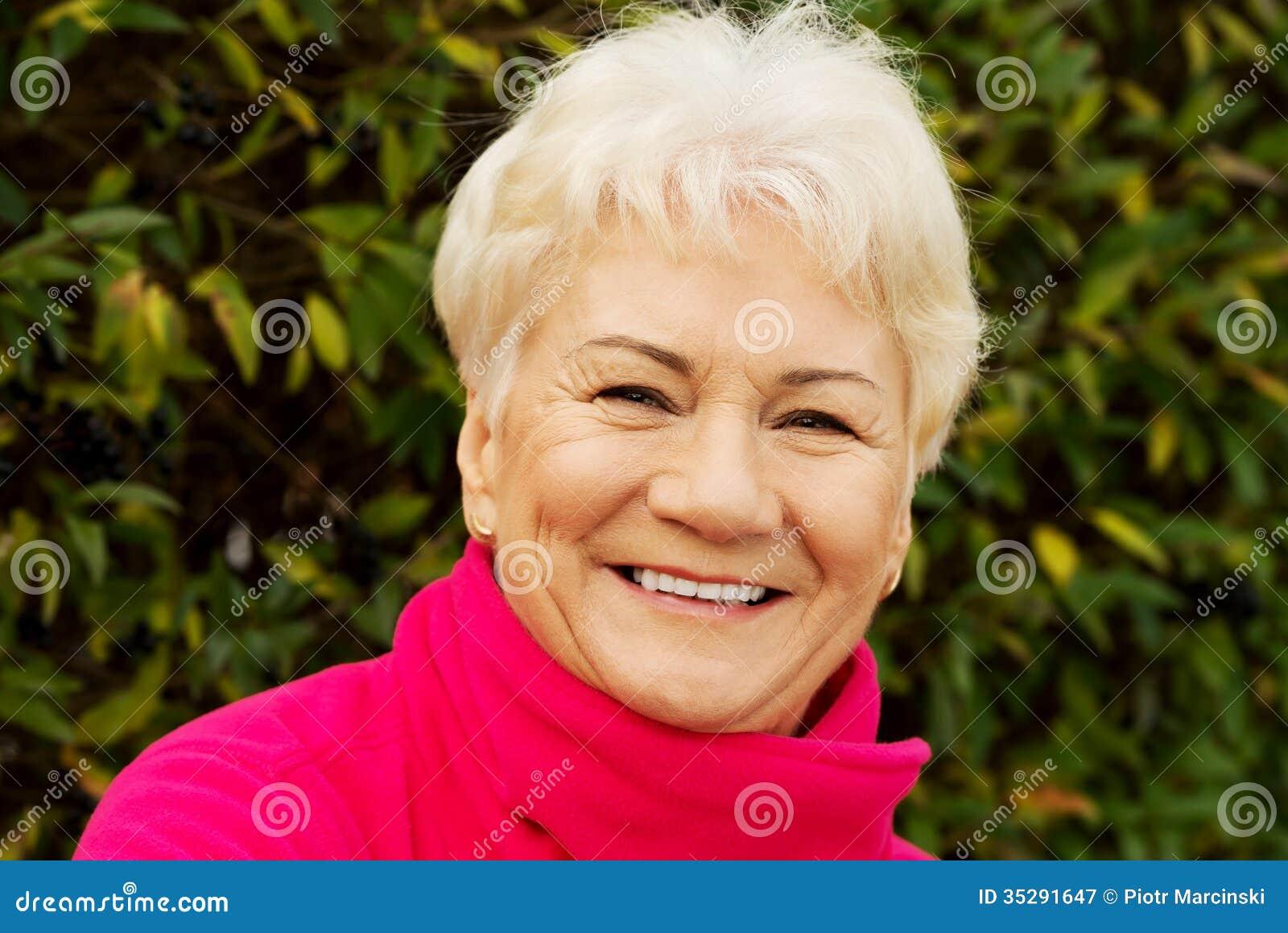 Stående av en gladlynt gammal dam över grön bakgrund.