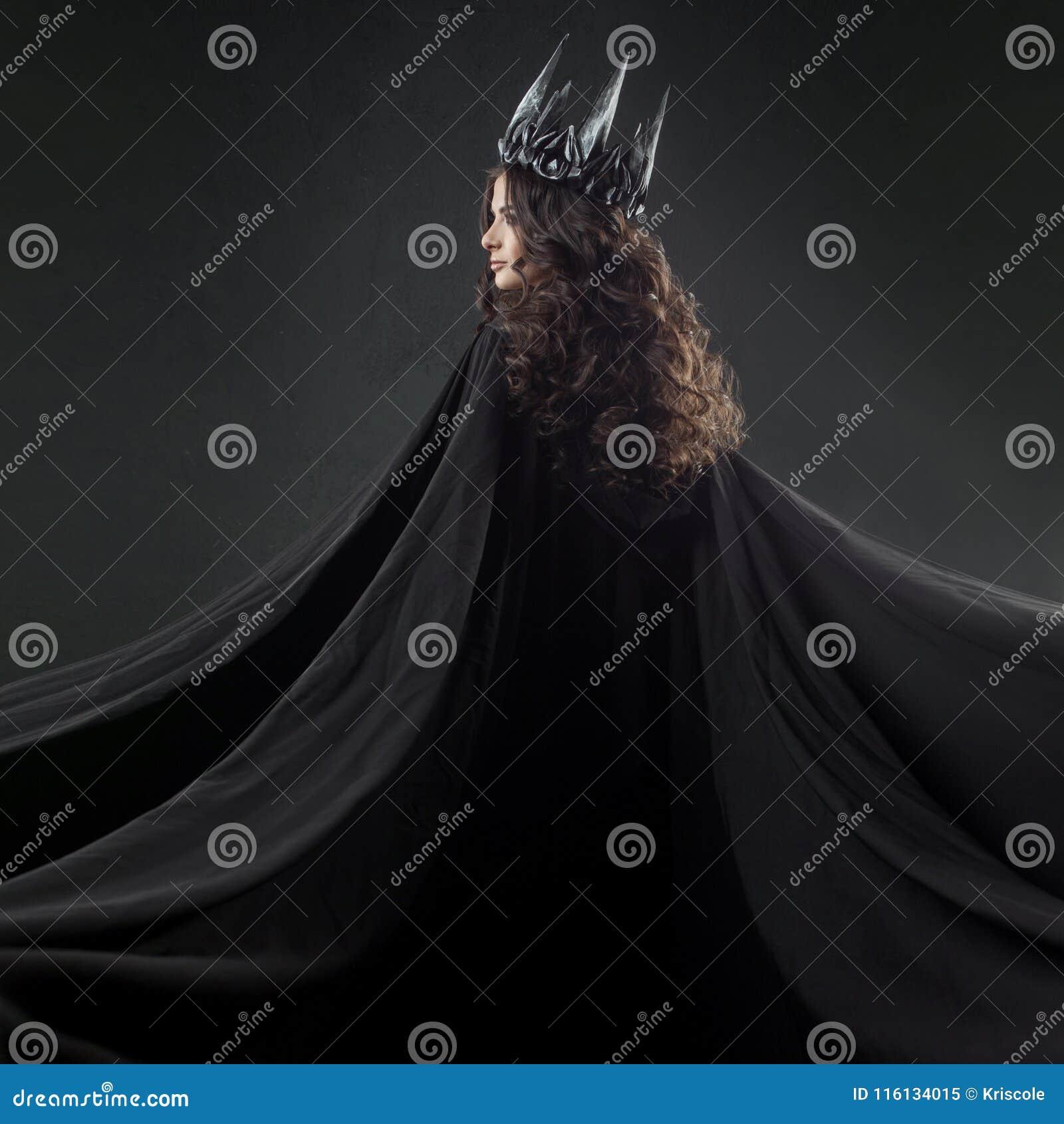 Stående av en gotisk prinsessa Härlig ung brunettkvinna i metallkrona och svart kappa
