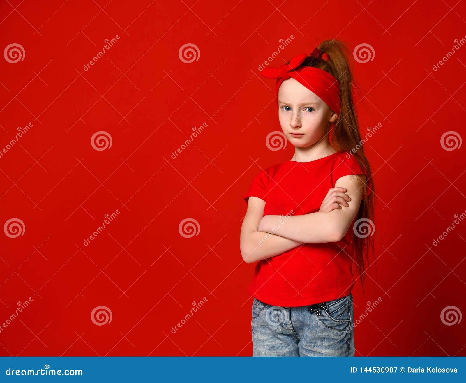 Stående av en gullig flicka som förargas i en röd väst som står med vikta händer och ser kameran
