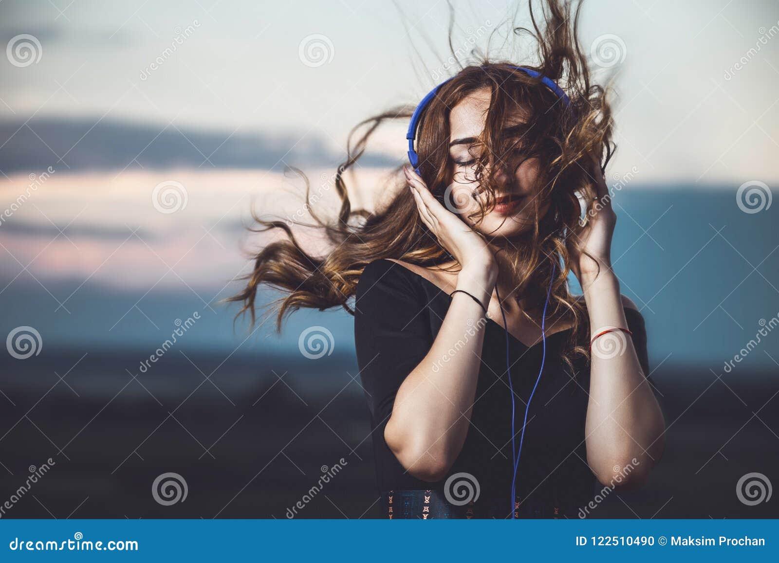 Stående av en härlig flicka i hörlurar som lyssnar till musik på naturen