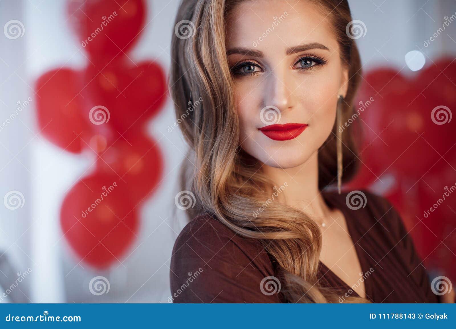 Stående av en härlig kvinna i dag för valentin` s på en bakgrund av röda luftballonger