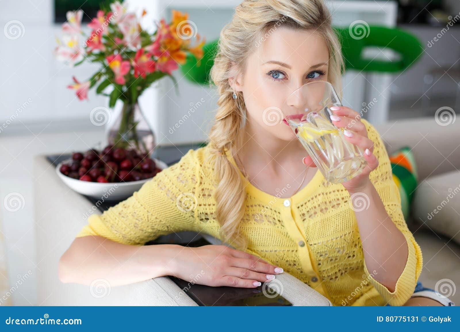 Stående av en härlig kvinna med ett exponeringsglas av vatten i köket