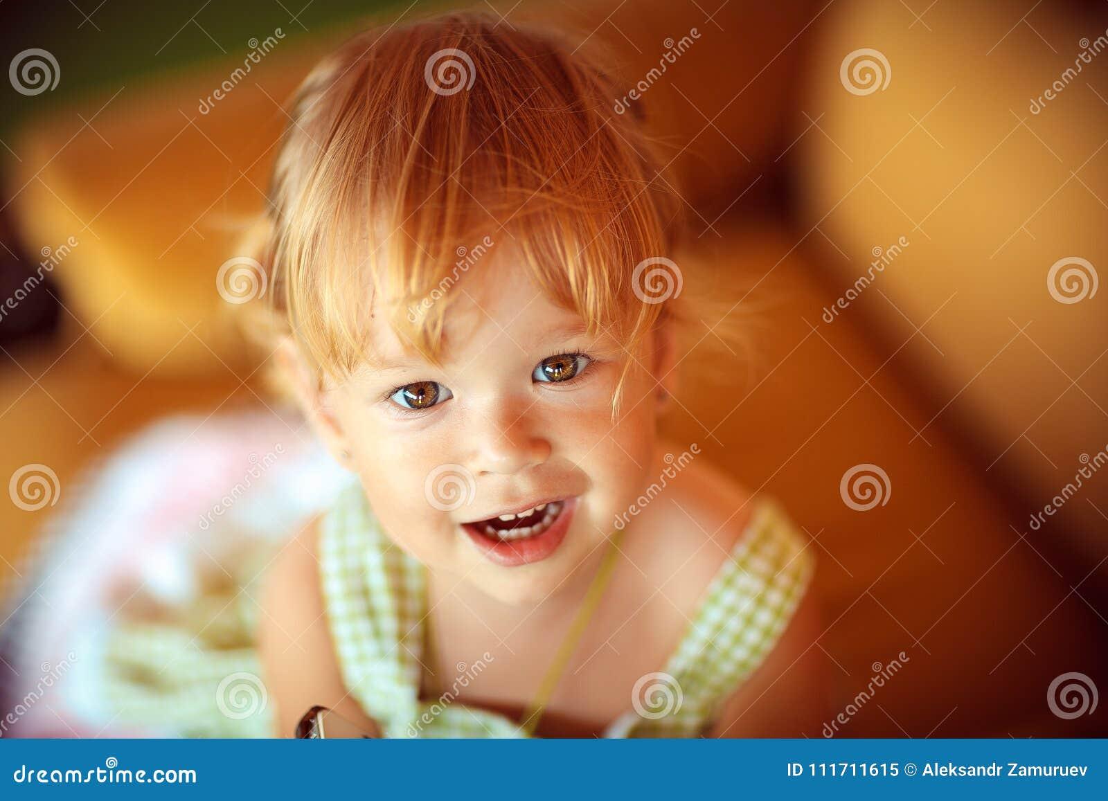 Stående av en härlig liten flicka som ser kameran Närbild