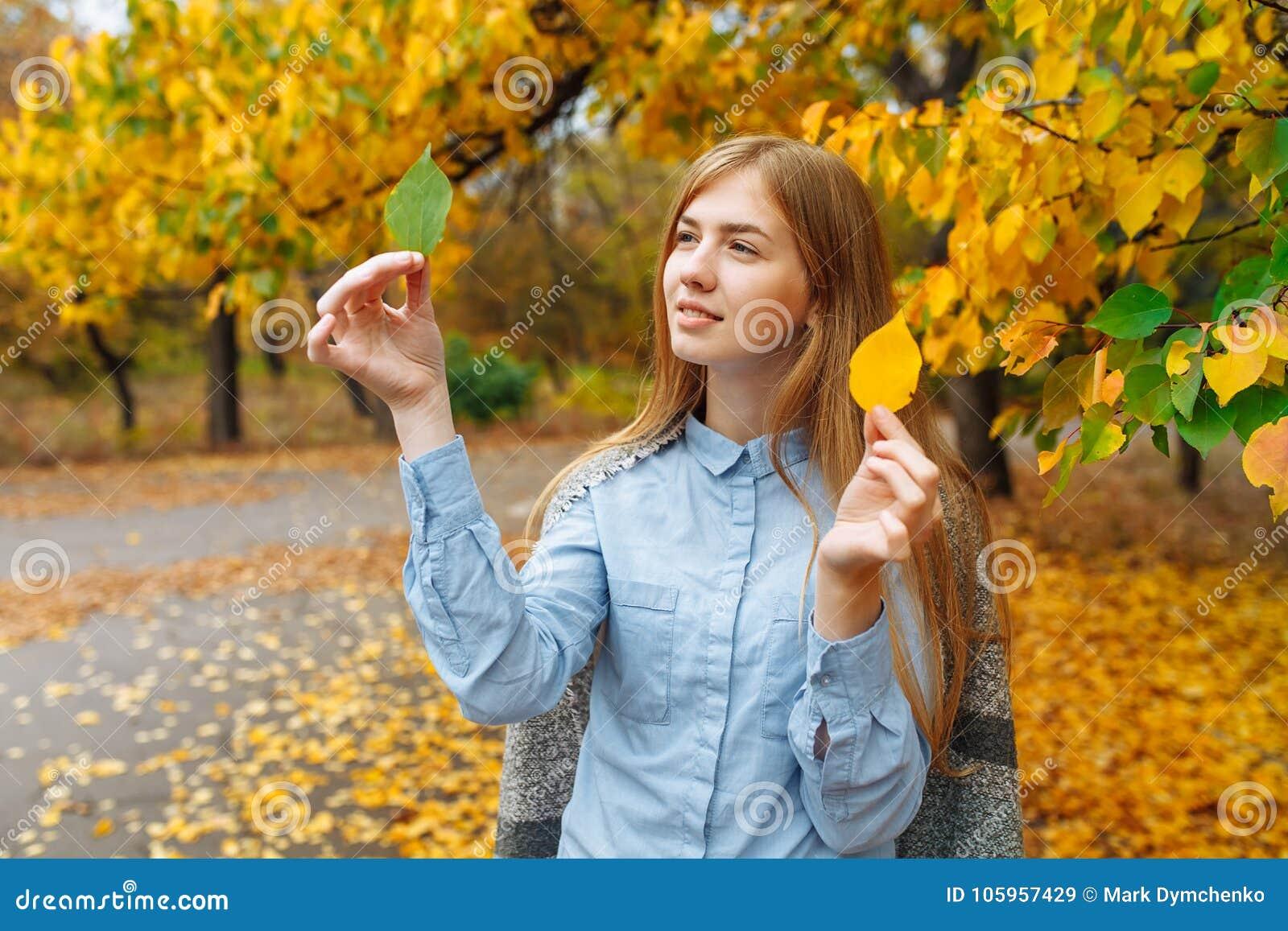 Stående av en härlig, söt gladlynt flicka som går i parkera i höstsäsong