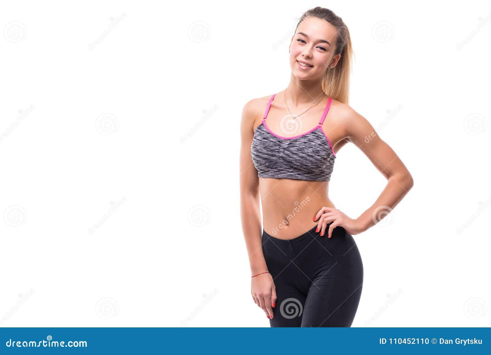 Stående av en härlig sportkvinna med händer på höfter på vit bakgrund