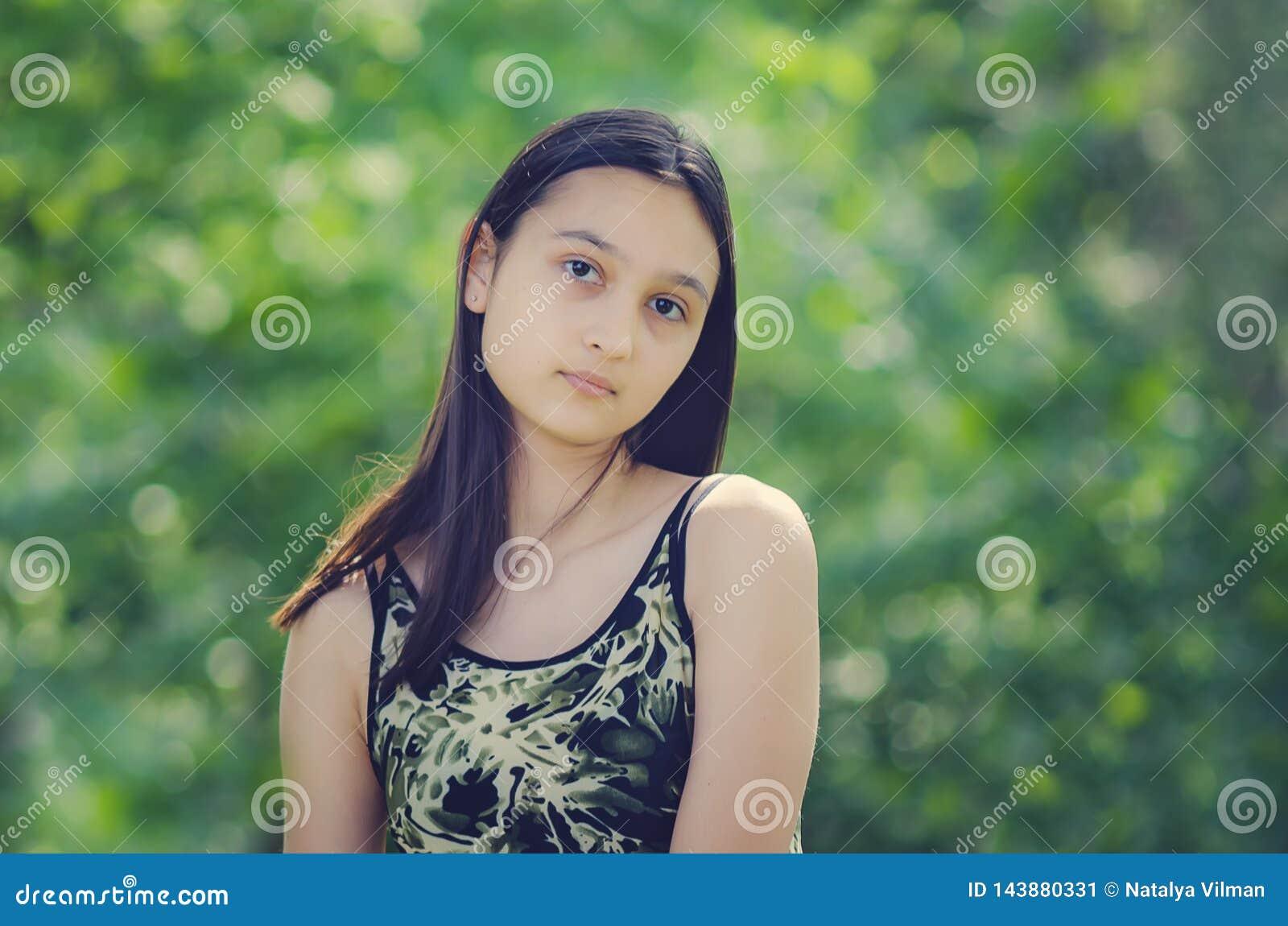 Stående av en härlig tonårs- flicka mot en bakgrund av grön lövverk