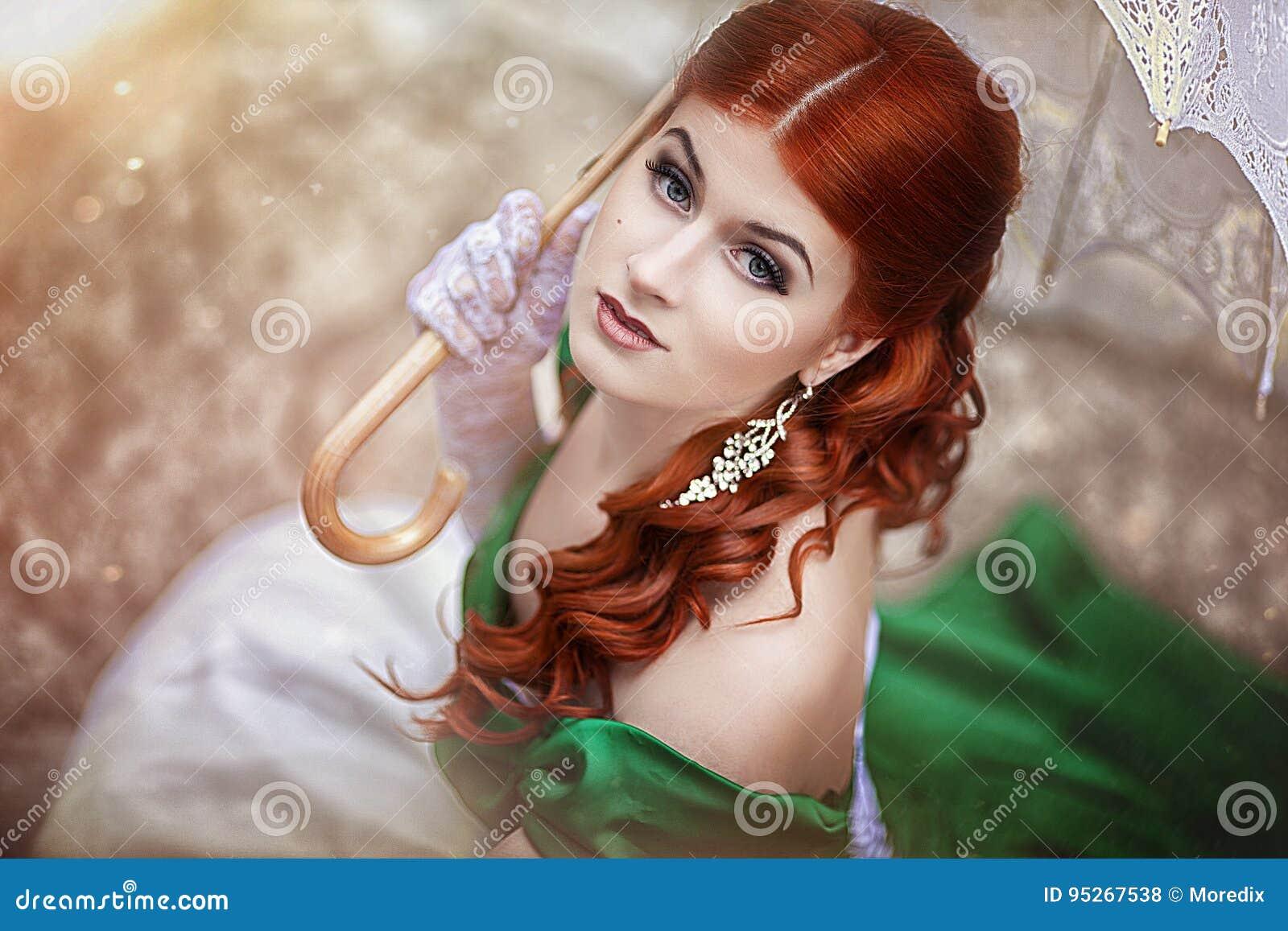 Stående av en härlig ung rödhårig flicka i en medeltida grön klänning med ett paraply Fantasiphotosession
