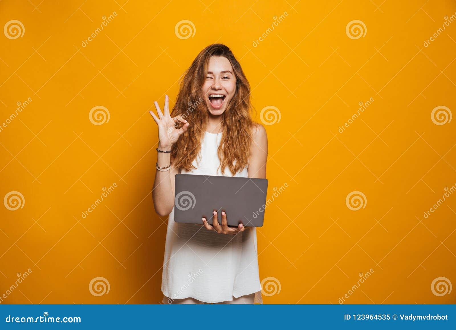 Stående av en hållande bärbar datordator för gladlynt ung flicka